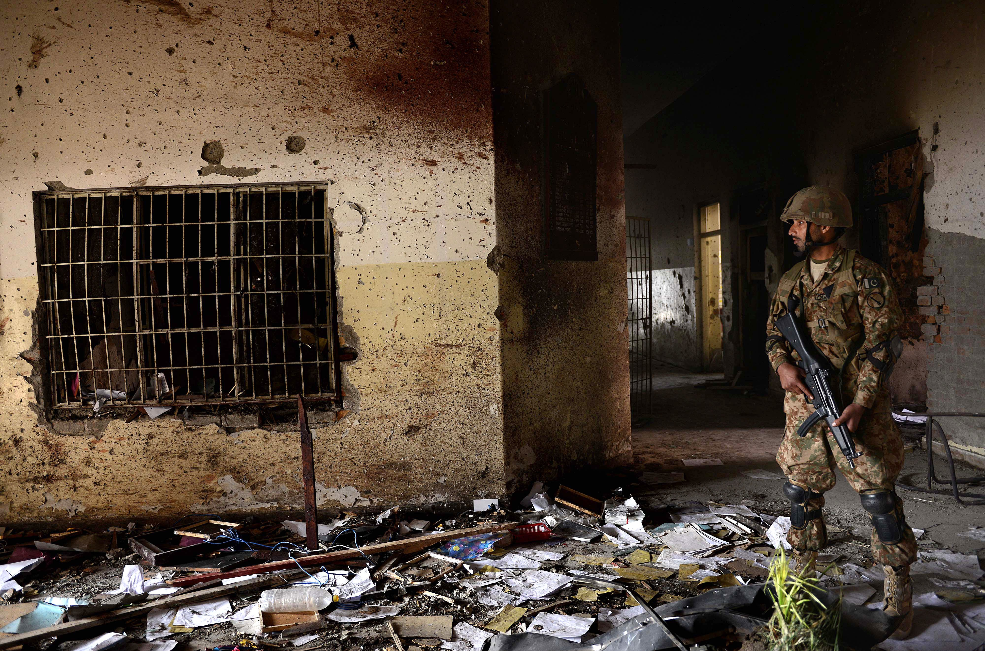 A Pakistani army soldier stands guard at the site of the militants' attack on the army-run school in Peshawar on December 18, 2014.