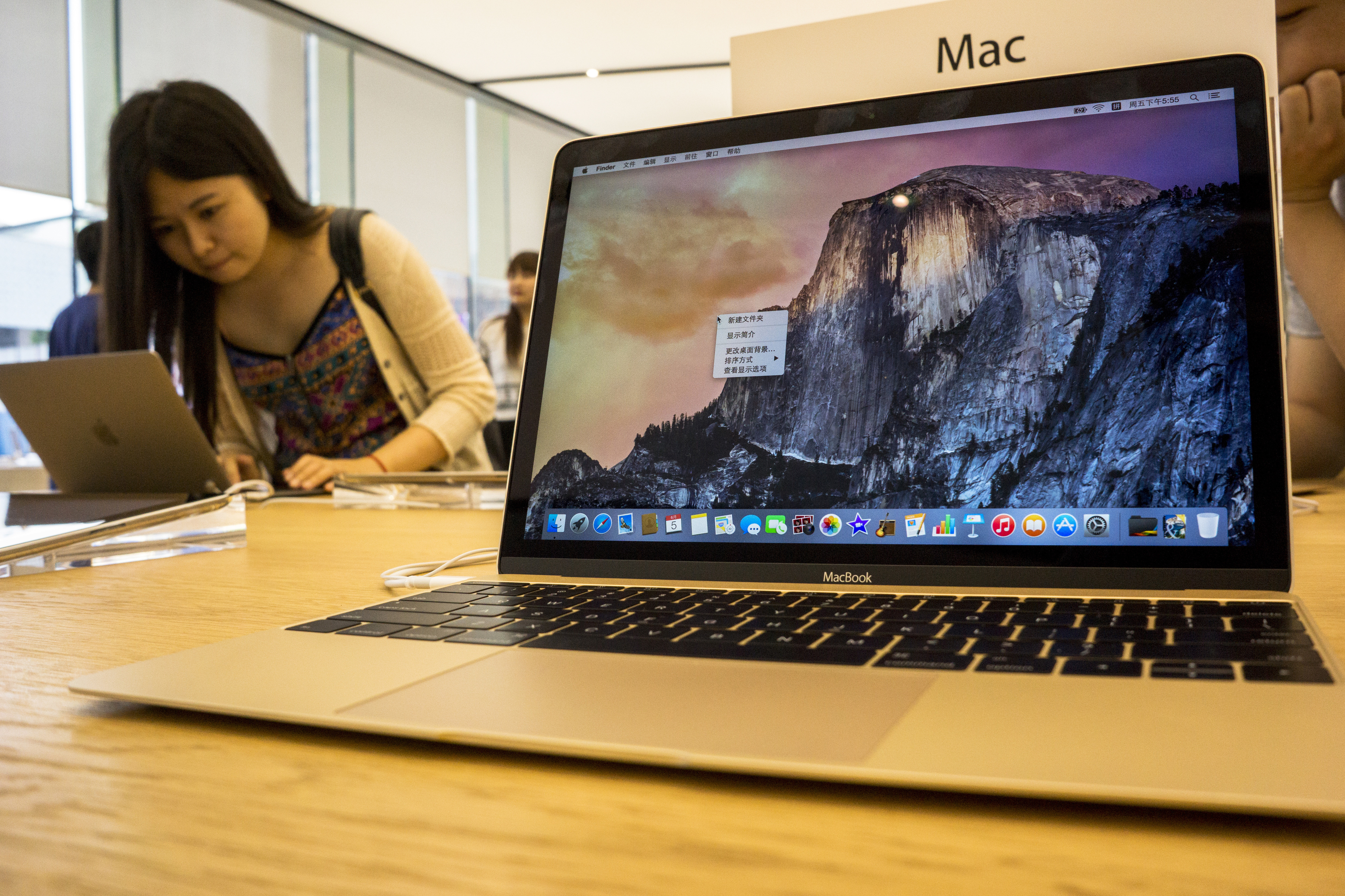 Chinese customers are experiencing and choosing Apple's products in an Apple store beside West lake in Hangzhou, which is the biggest Apple store in Asia.