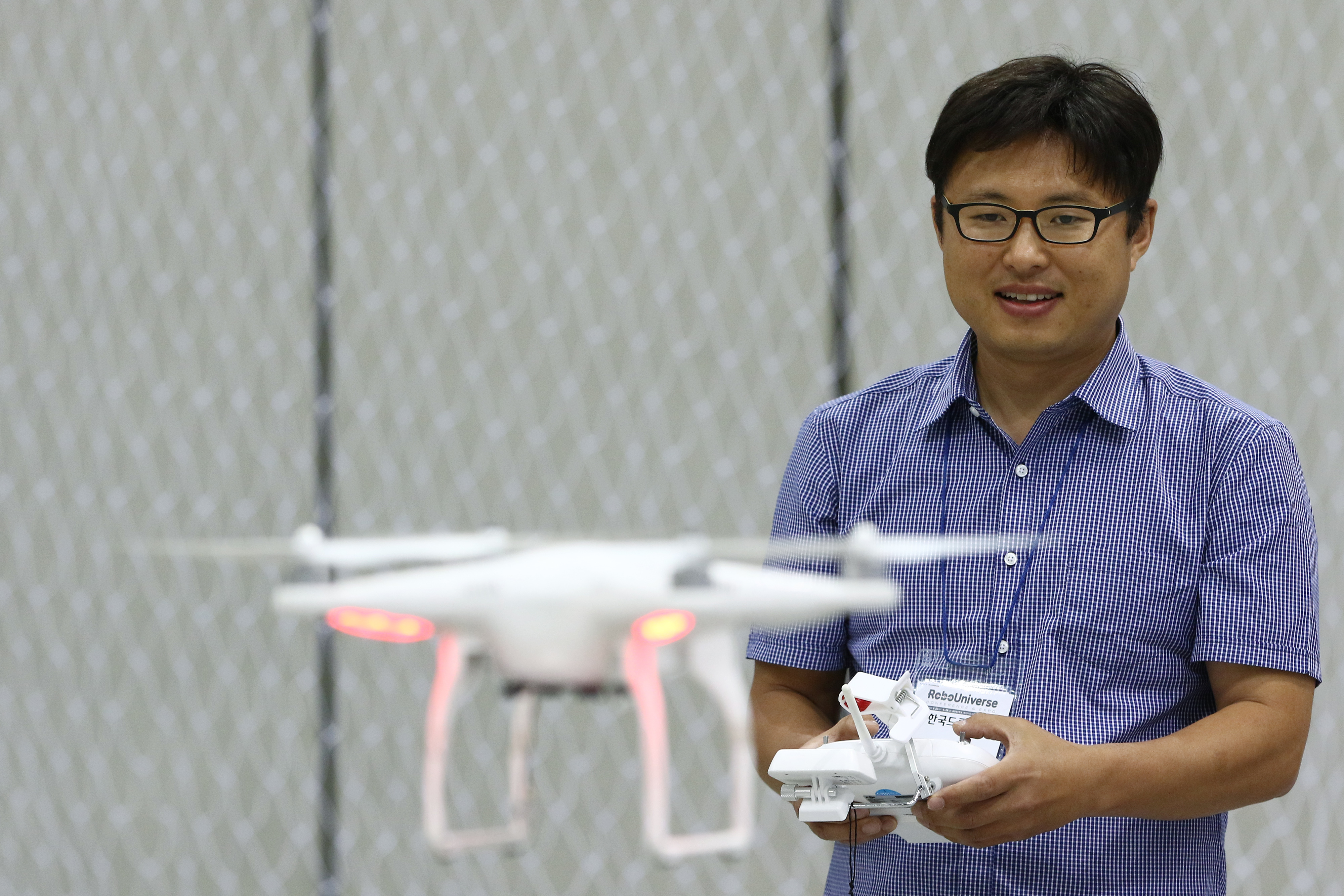 An attendee flies a Phantom 2 drone developed by SZ DJI Technology Co. at the RoboUniverse Conference & Expo in Goyang, South Korea, on Wednesday, June 24, 2015.