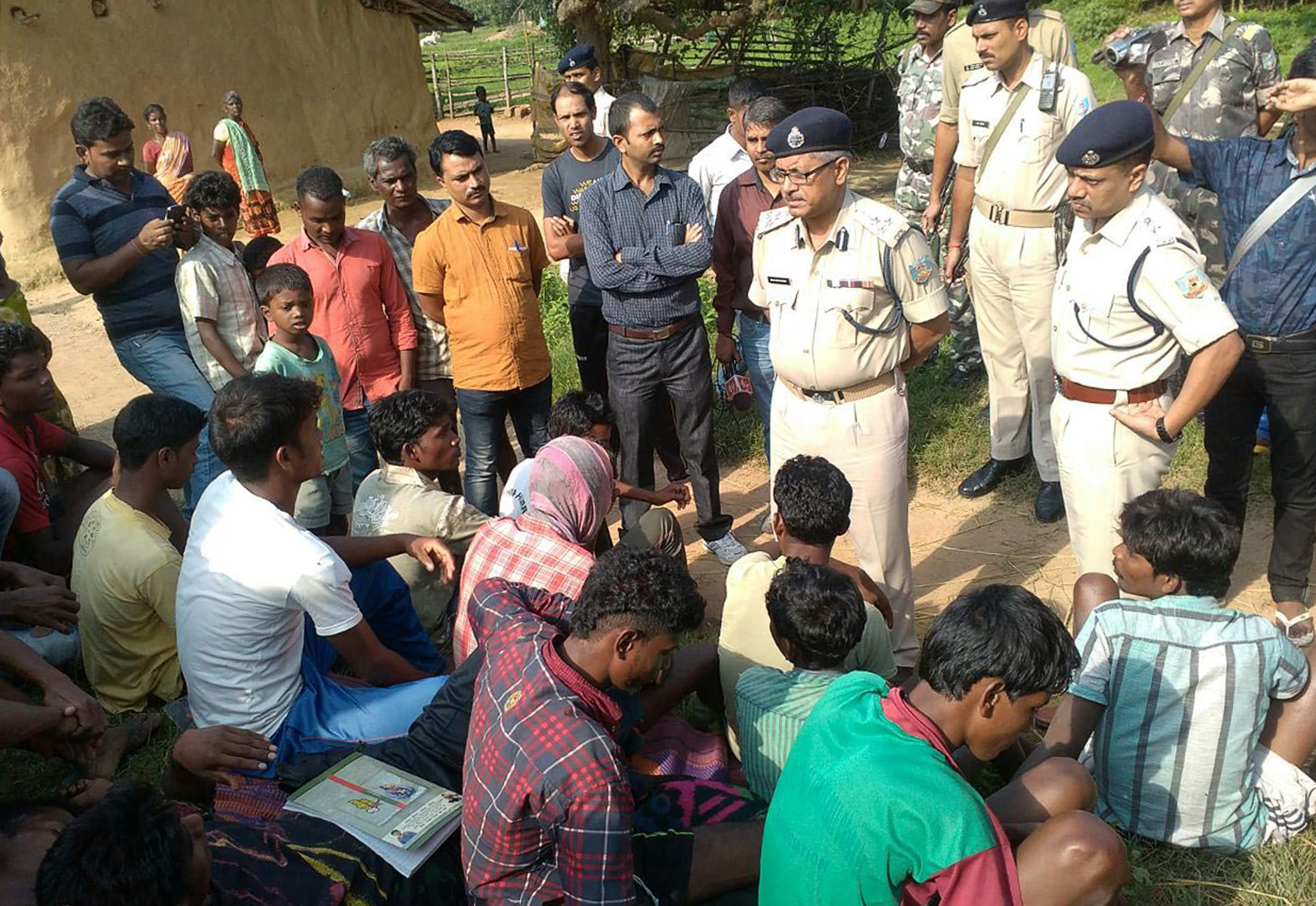 Indian police talk to villagers after five women accused of practicing witchcraft were killed in Kanjia village in India's eastern Jharkhand state on Aug. 8, 2015