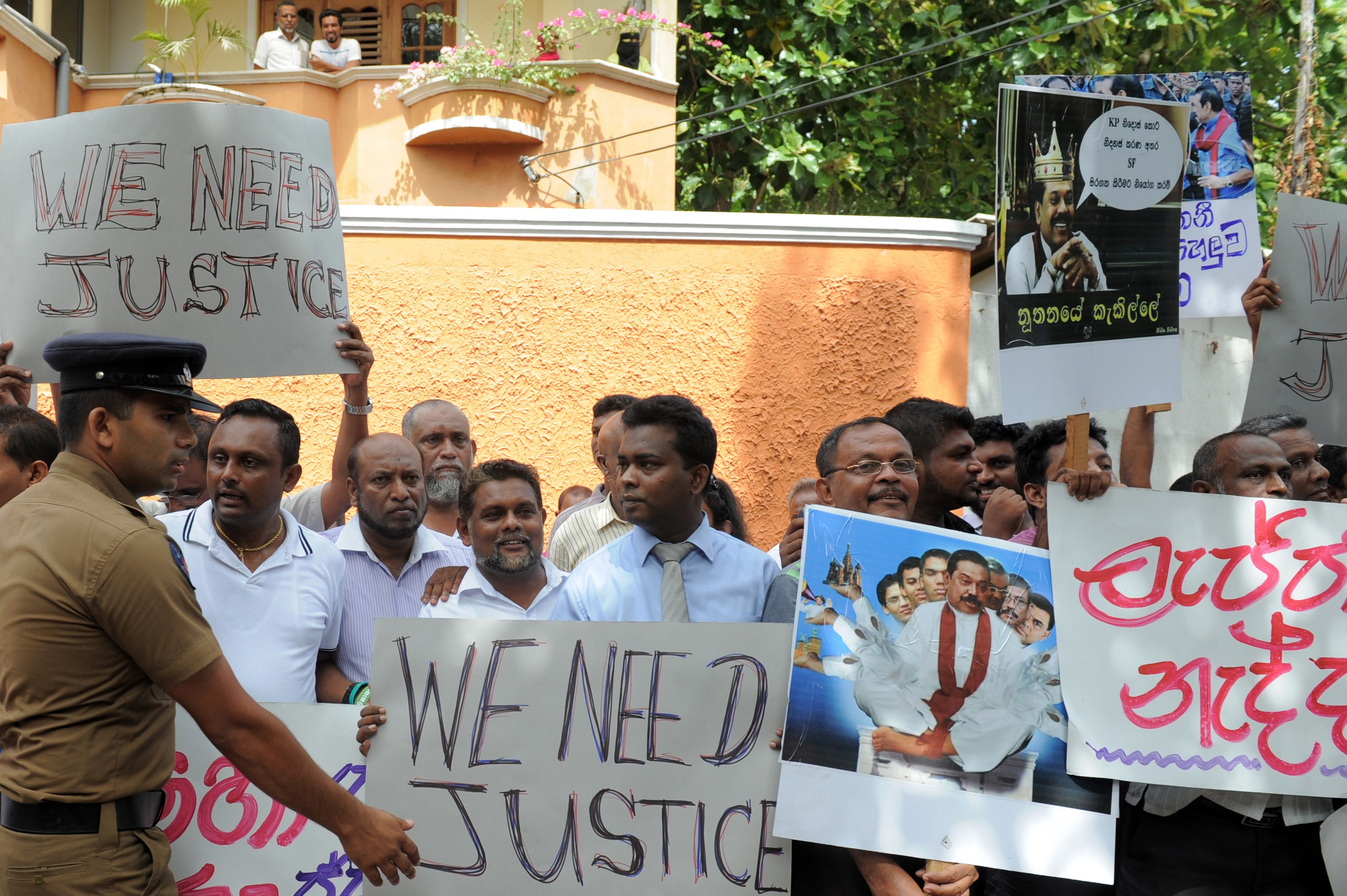 Anti-Rajapakse activists carried placards denouncing the former leader and his administration as the remains of Sri Lankan rugby player Wasim Thajudeen leave the burial ground of the Dehiwela mosque in Colombo on August 10, 2015, after the body was exhumed to be sent to the Judicial Medical Officer.
