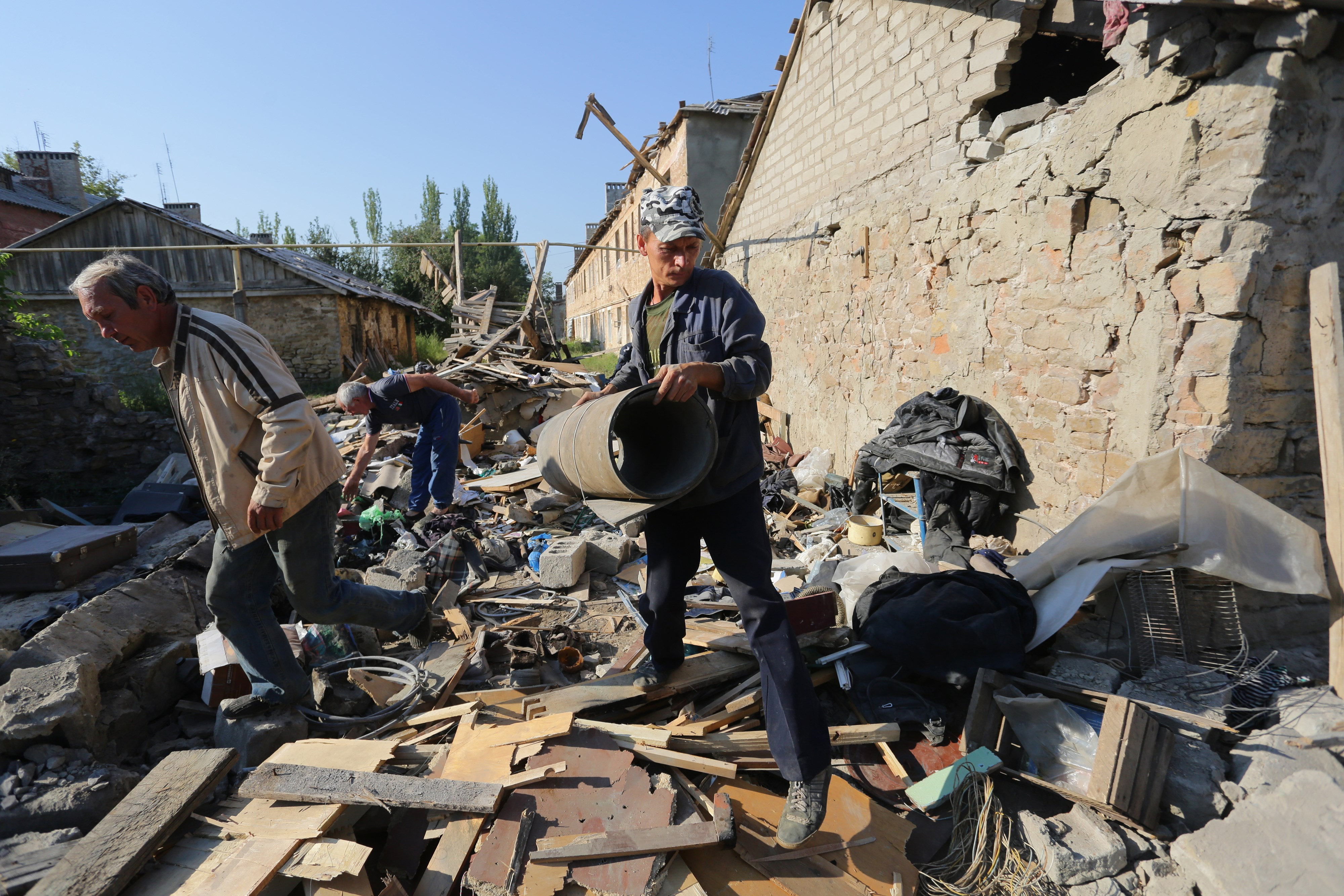 Residents clean up the debris of their destroyed house after shelling between Ukrainian forces and pro-Russian separatists on August 10, 2015 in Golmovsky village, Donetsk region.