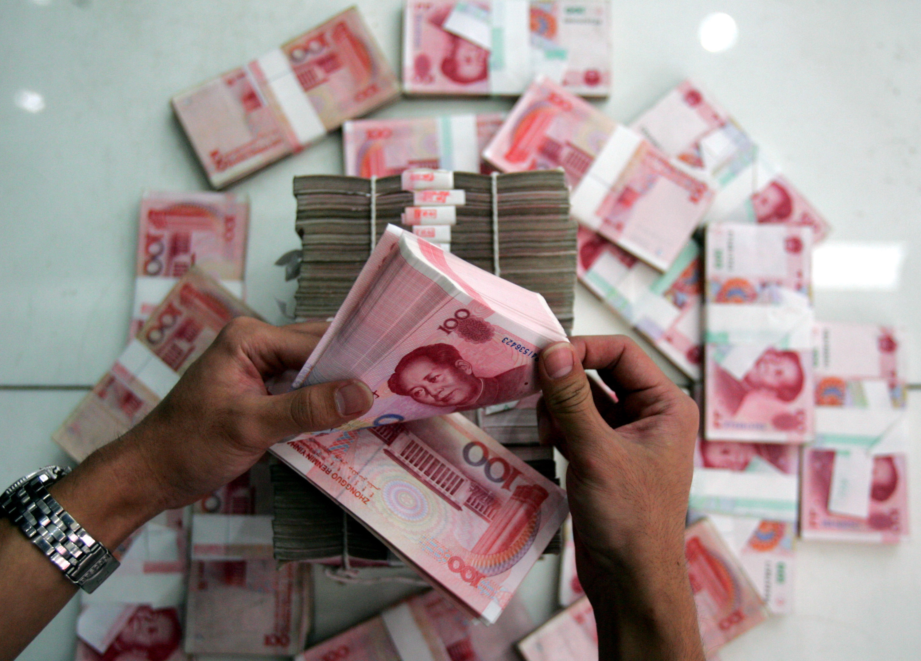 A clerk counts stacks of Chinese yuan at a bank on July 22, 2005 in Beijing, China.