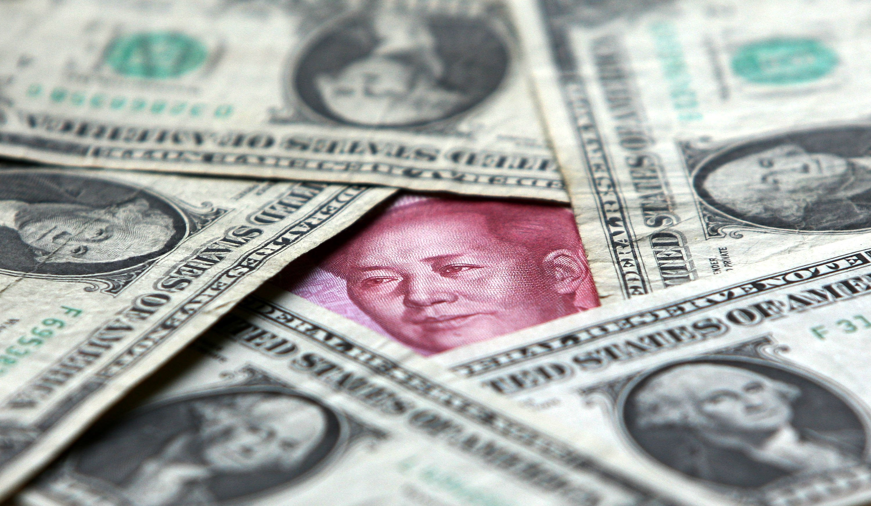 Dollars and yuan notes are seen at a bank on May 15, 2006 in Beijing.