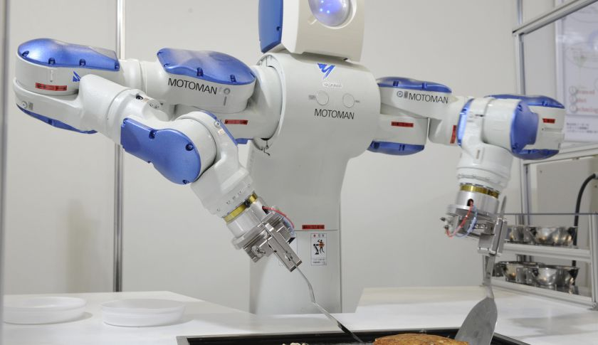 Japanese giant Yaskawa Electric's industrial robot Motoman turns over a pancake on a hot plate.