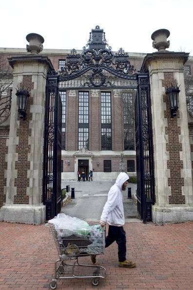 A man collecting empty bottles walks past a gate leading to Harvard Yard on the Harvard University campus in Cambridge, Mass. on Dec. 15, 2009.