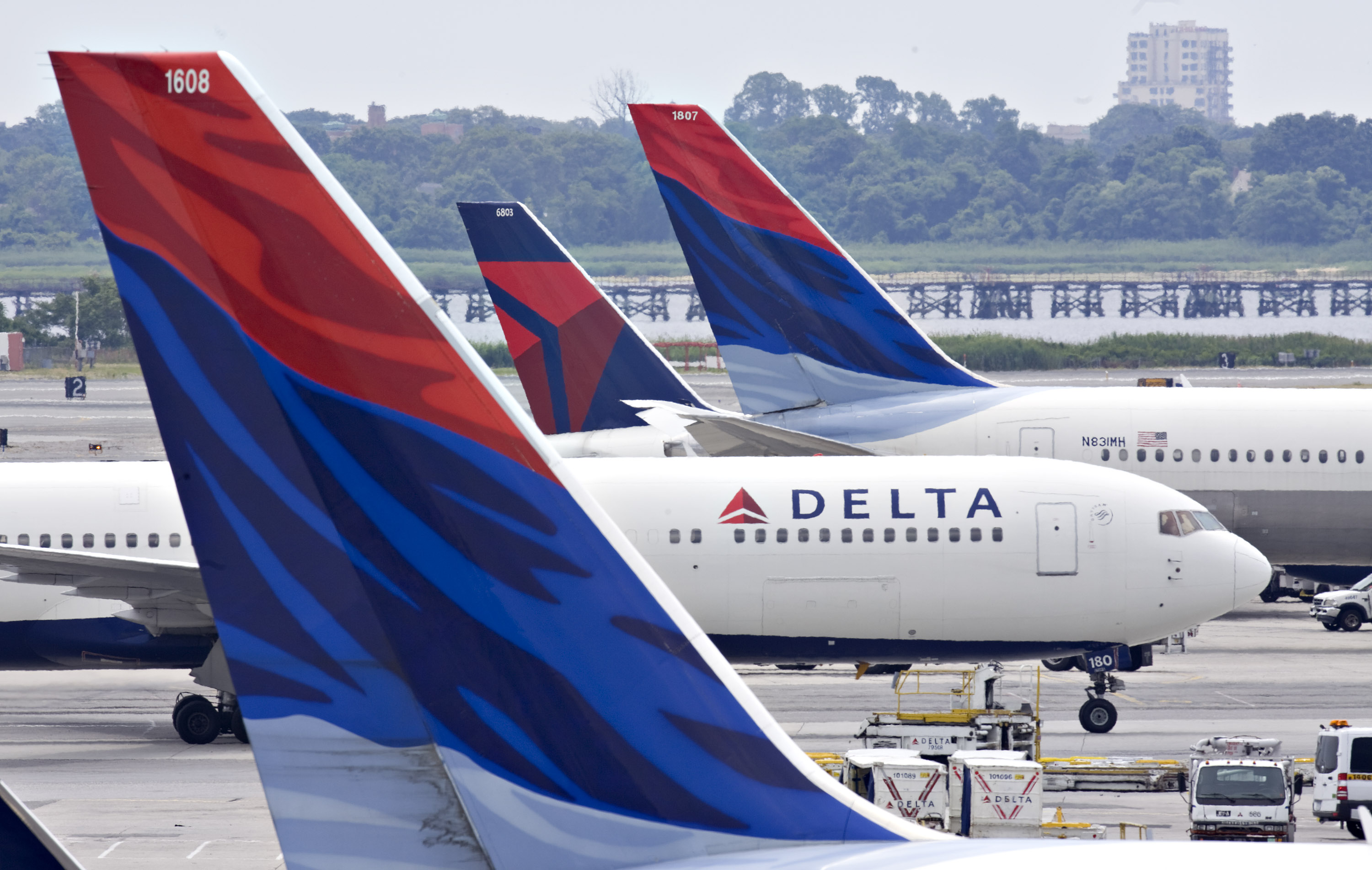 A Delta Air Lines plane taxis toward a gate between other Delta planes at John F. Kennedy International Airport in New York, U.S., on Monday, July 20, 2009.