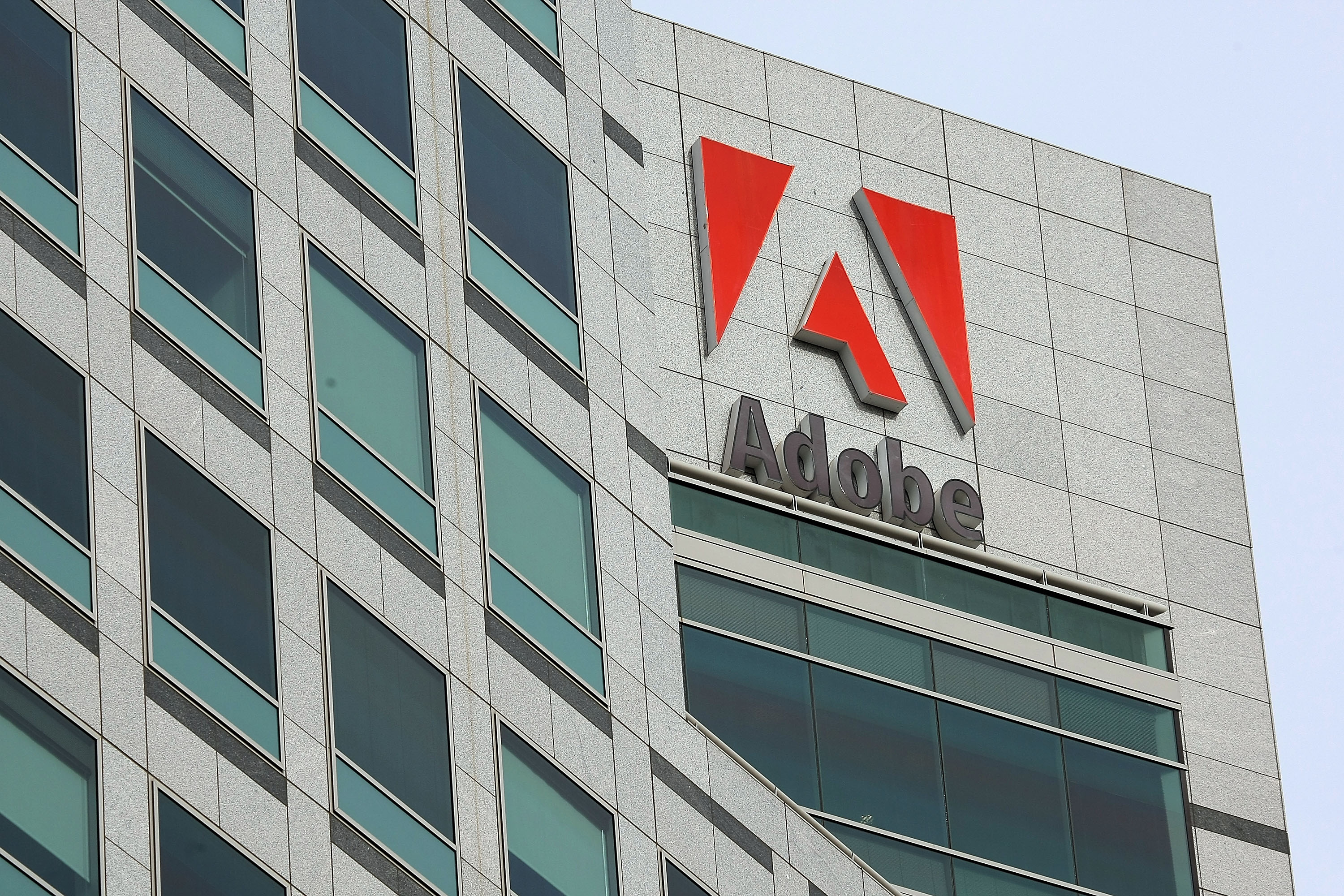 The Adobe logo is displayed on the side of the Adobe Systems headquarters January 15, 2010 in San Jose, California. Adobe Systems has added 20 new wind turbines to their rooftops in an attempt to harness wind energy to help power their offices.