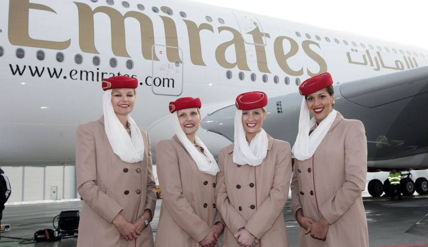 Emirates stewardesses pose in front of an aircraft.