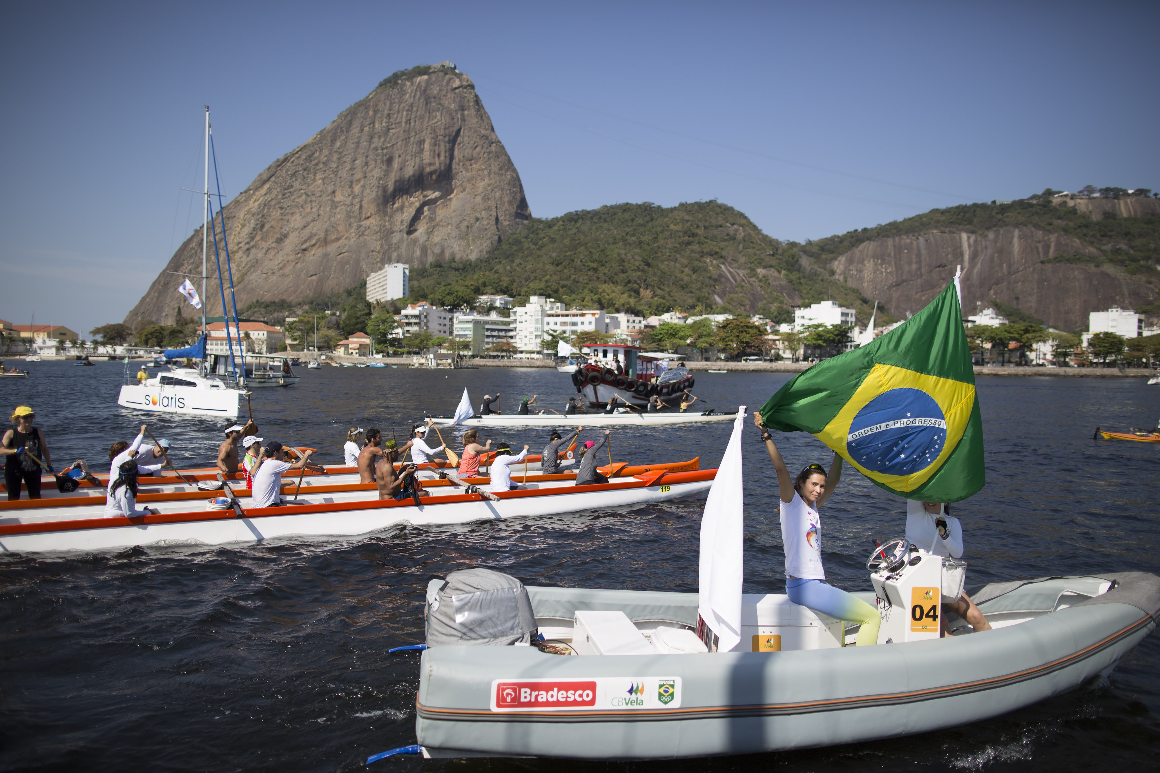 A woman flies Brazil's national flag on a boat during a protest in the Marina da Gloria in Rio de Janeiro on Aug. 8, 2015.