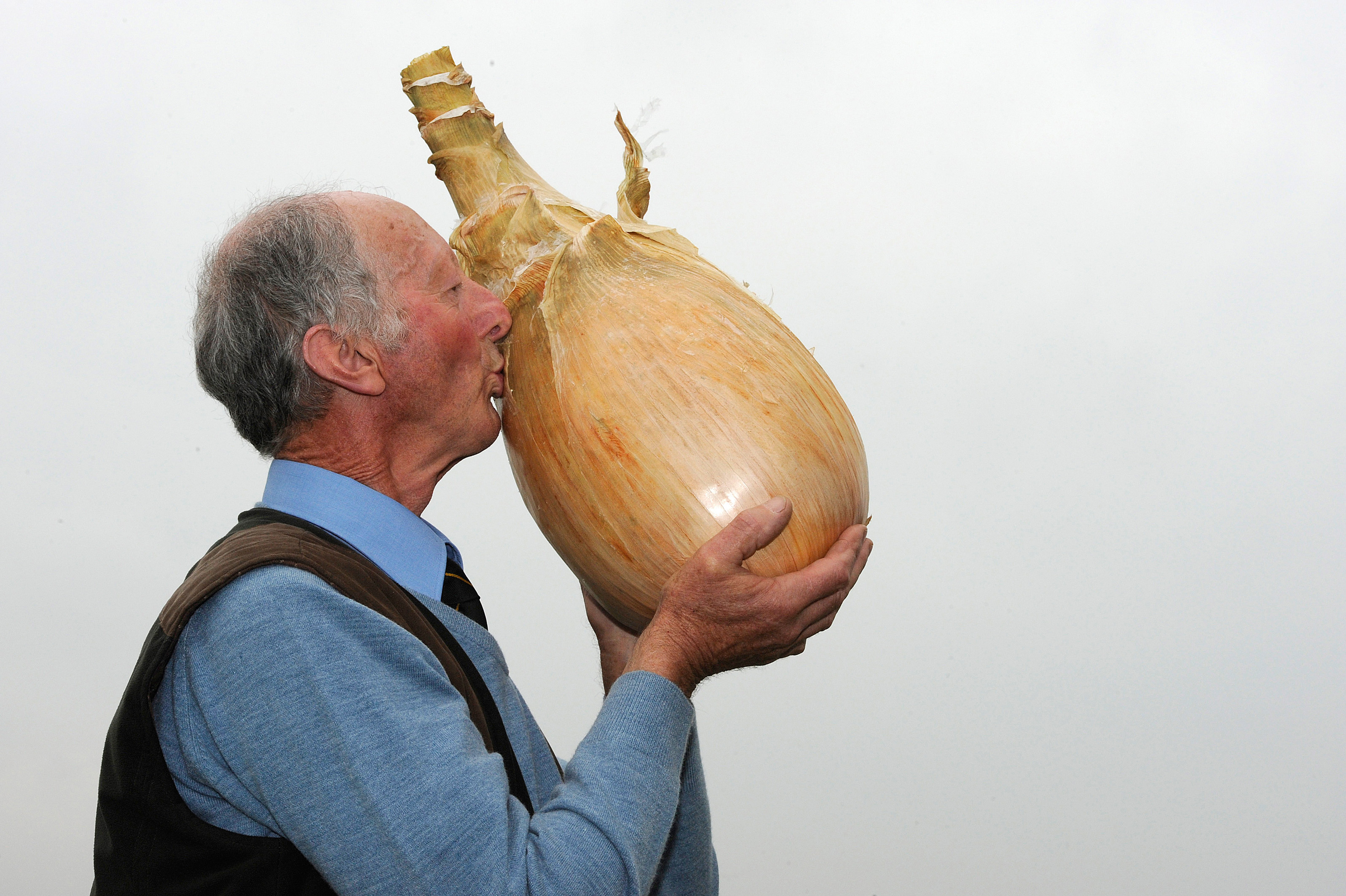 Grower Pete Glazebrook poses for photographers with his onion weighing 17lb 15.5oz  at the Harrogate Autumn Flower Show in Harrogate, northern England September 16, 2011.