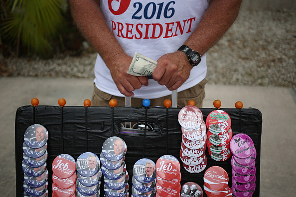 A vendor holds money while selling buttons and t-shirts outside an event where Former Governor of Florida Jeb Bush announced he will seek the 2016 Republican presidential nomination on the Kendall Campus of Miami Dade College in Miami, Florida, U.S., on Monday, June 15, 2015. In an attempt to follow his brother and father into the nation's highest office, Bush announced today that he's running for president of the United States. Photographer: Luke Sharrett/Bloomberg via Getty Images
