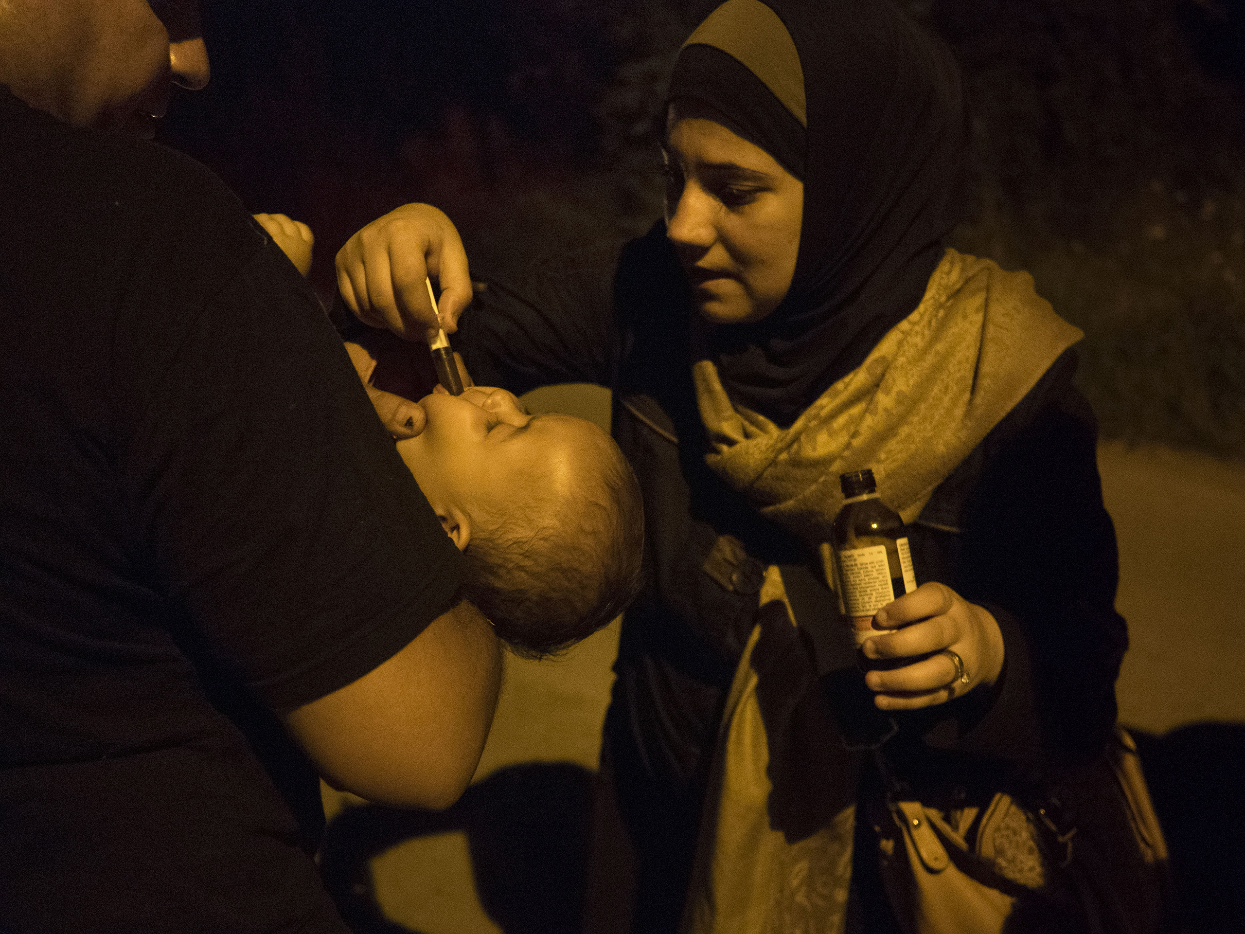 Horgos, Serbia. August 12, 2015.                                   Syrian families walk at night toward the border to attempt to cross it. A woman gives medicine to young children exhausted by days and weeks of walking.