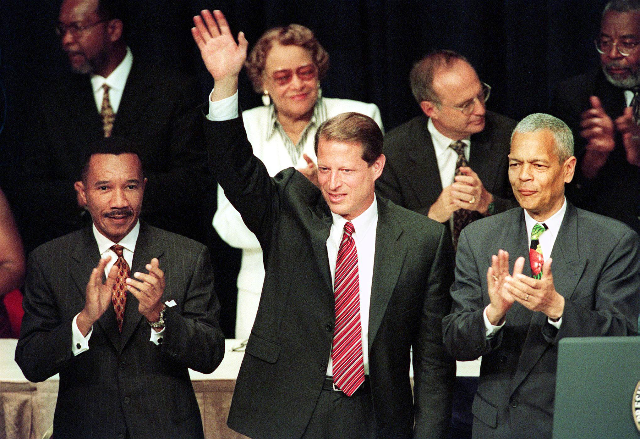 Vice President Al Gore waves to the audience with Kweisi Mfune, President of the National Association for the Advancement of Colored People (NAACP), and Julian Bond, chairman of the board of the NAACP, on July 15, 1999, in New York City at the 90th Annual NAACP convention.