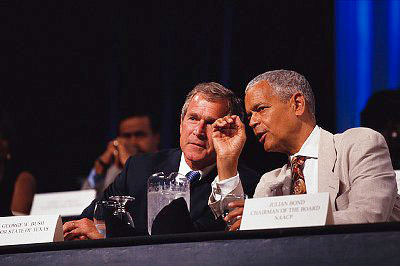 During his presidential campaign, George Bush talks with Julian Bond, chairman of the NAACP, at a NAACP convention in Baltimore on July 10, 2000.