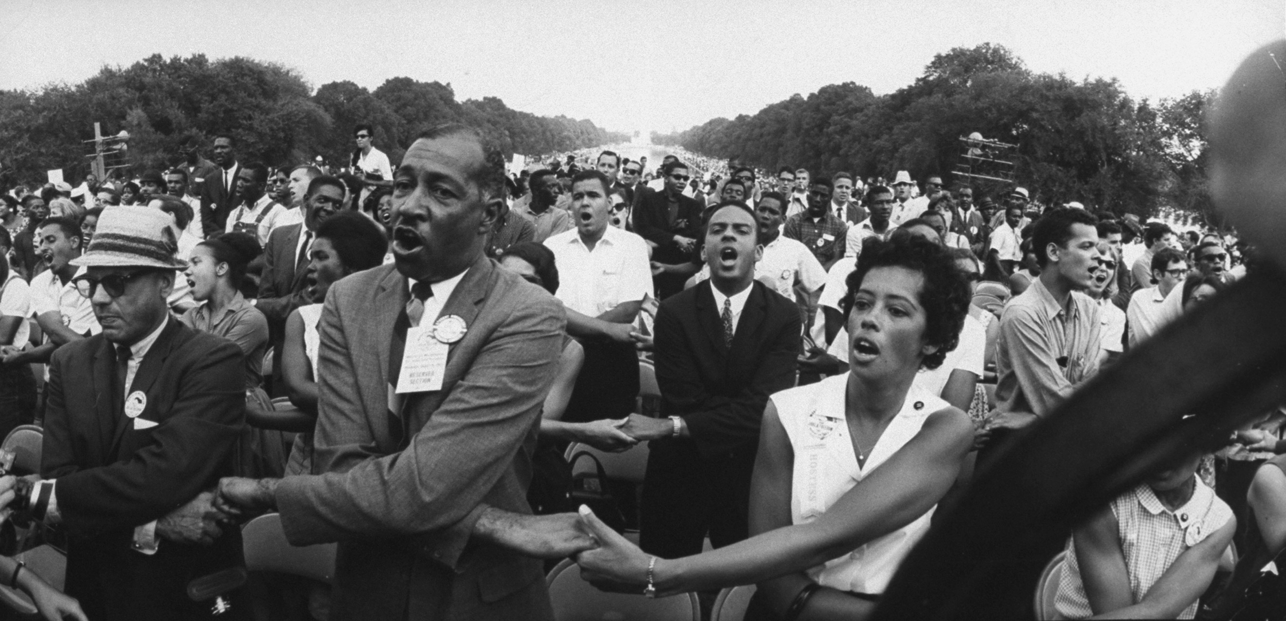 Civil rights activists Julian Bond (right) and Andrew J. Young (center), hold hands during the March on Washington in front of the Washington Monument in August 1963.