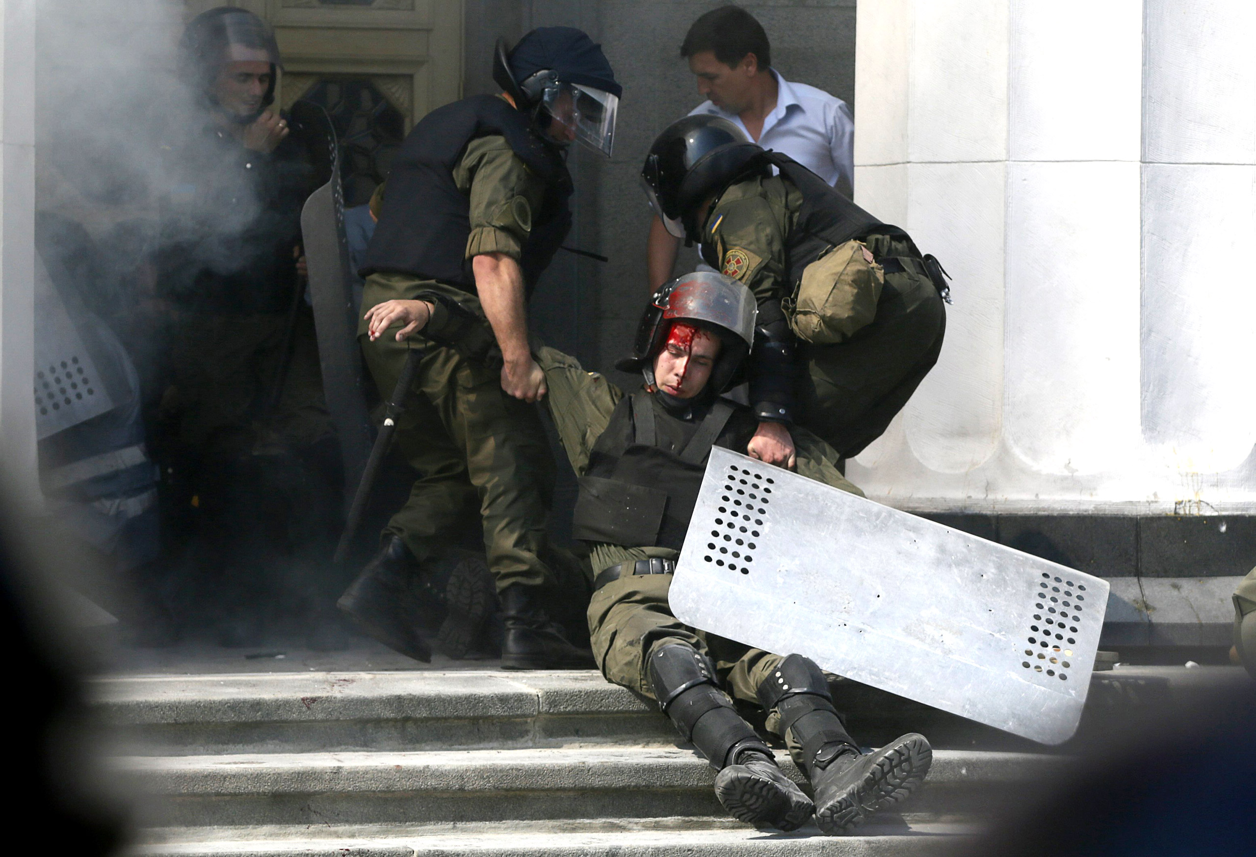 An injured national guard officer is carried away by colleagues outside the parliament building in Kiev, Ukraine, on Aug. 31, 2015.