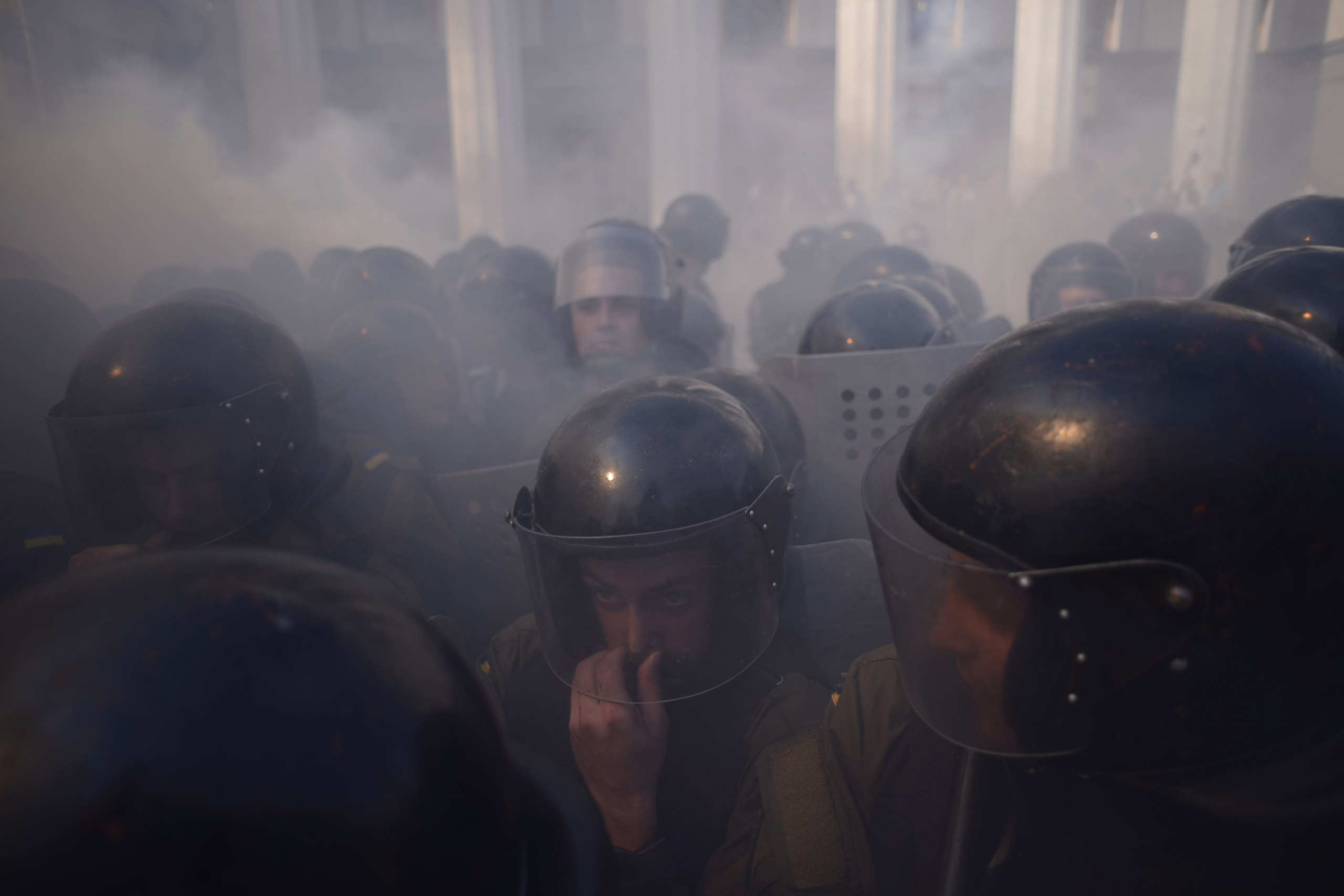 Police stand among rising smoke near the parliament building in Kiev, Ukraine, on Aug. 31, 2015.