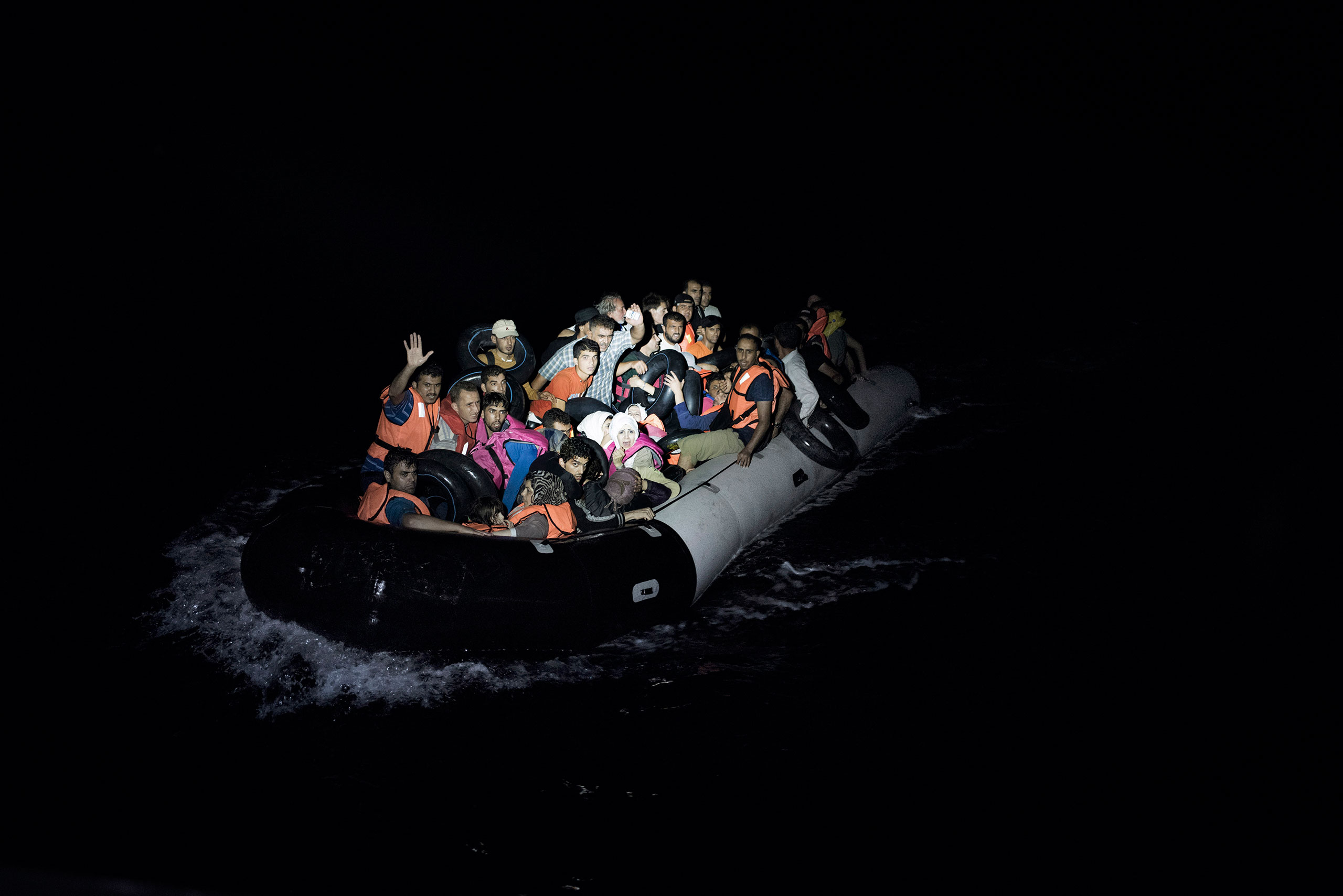 A boat full of migrants is illuminated by the flashlights of Greek coast guards who have come to rescue them from the waters near the Greek-Turkish border. Sept. 6, 2015.From  One Night on Migrant Patrol With the Greek Coast Guard