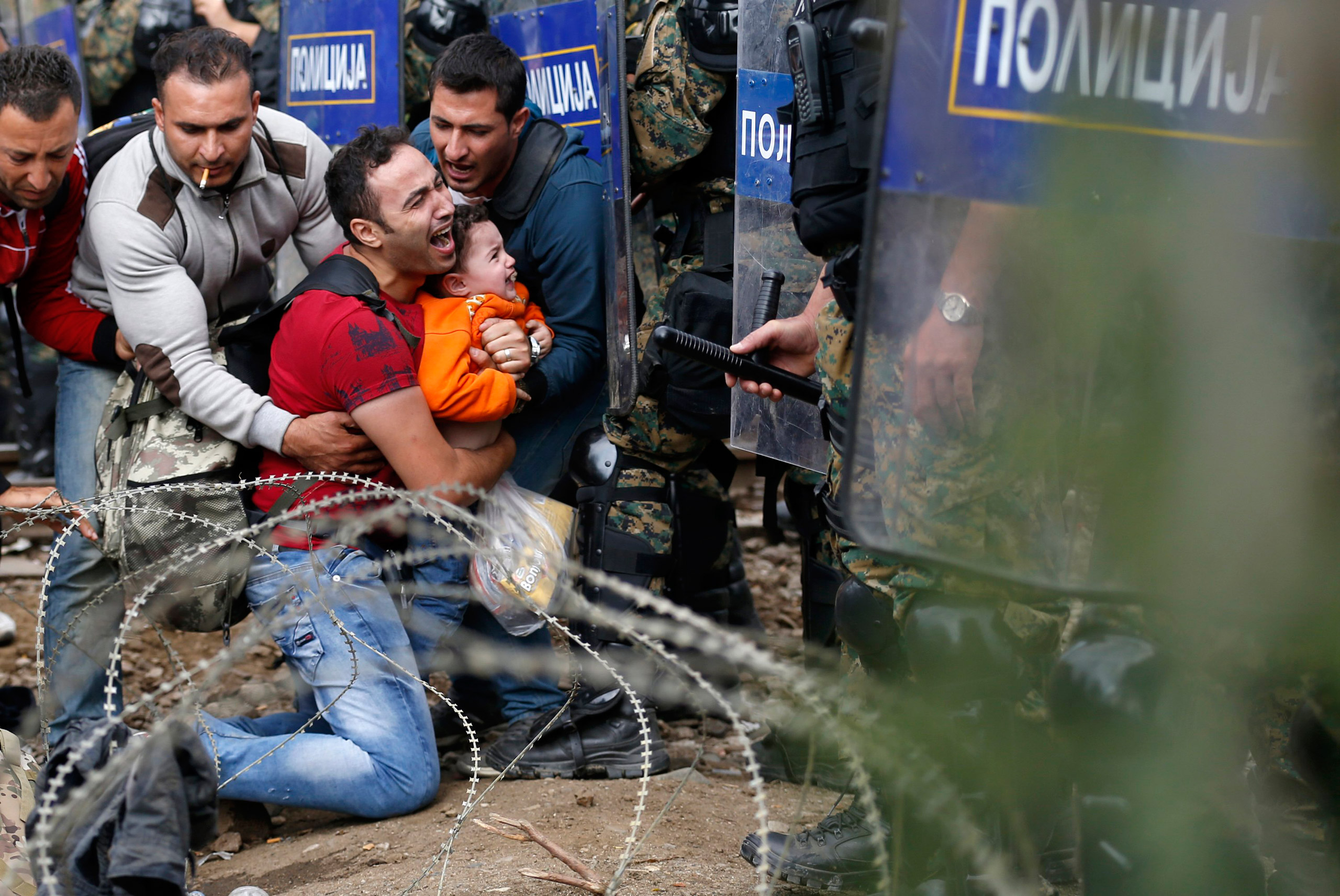 Men help a fellow migrant as they are stuck between Macedonian riot police officers and other migrants during a clash near the border train station of Idomeni, northern Greece. They are waiting to be allowed by the Macedonian police to cross the border from Greece to Macedonia, on Aug. 21, 2015.