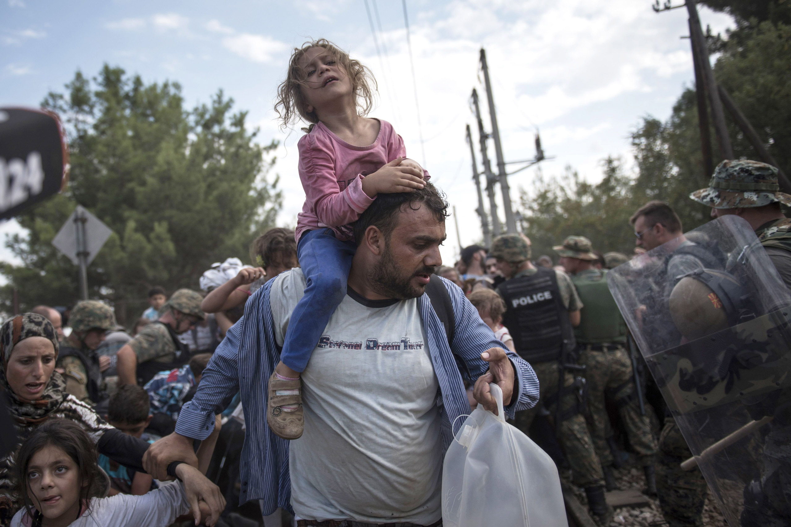 A migrant child and her father pass through a cordon of policeman and manage to enter Macedonia, after being held in the border zone between Greece and Macedonia, on Aug. 21, 2015.