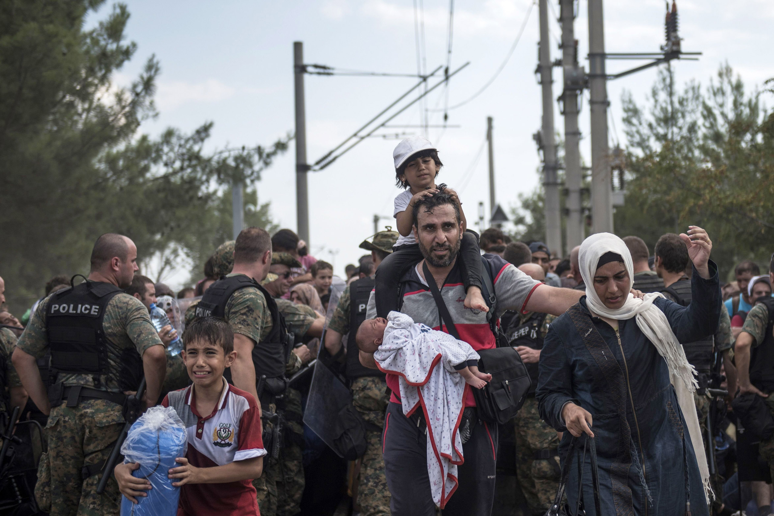 A family of migrants enters Macedonia after being held in the border zone, since the country had declared emergency and closed its south border with Greece, on Aug. 21, 2015.