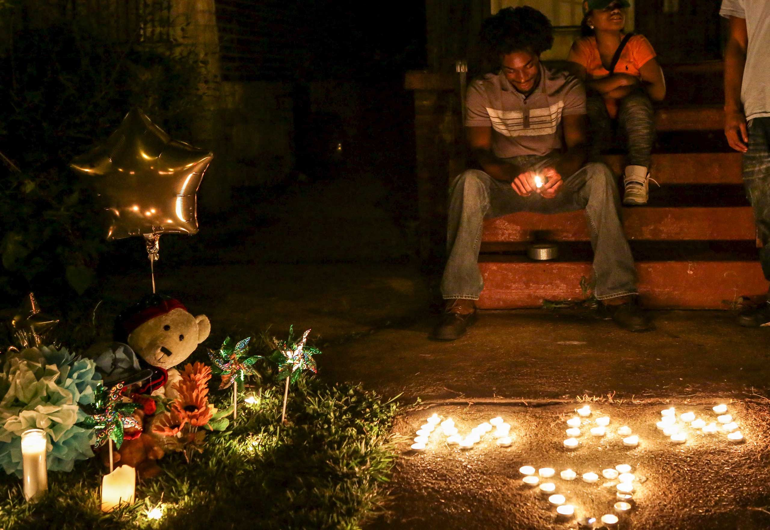 Chris Ball-Bey, the brother of Mansur Ball-Bey, sits by his brother's memorial after a candlelight vigil on Walton Ave in St. Louis, Mo., on Aug. 20, 2015.