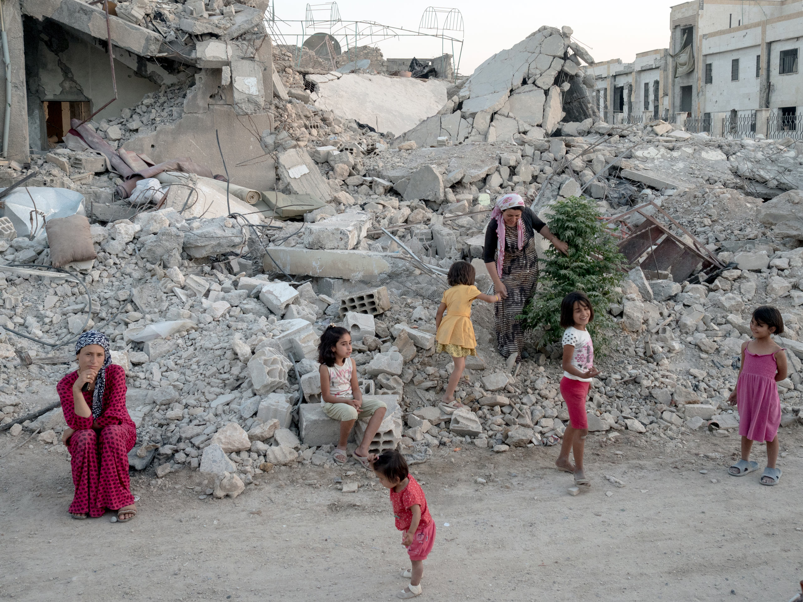A family stands on what is left of their home. Kobani, Syria. Aug. 6, 2015.