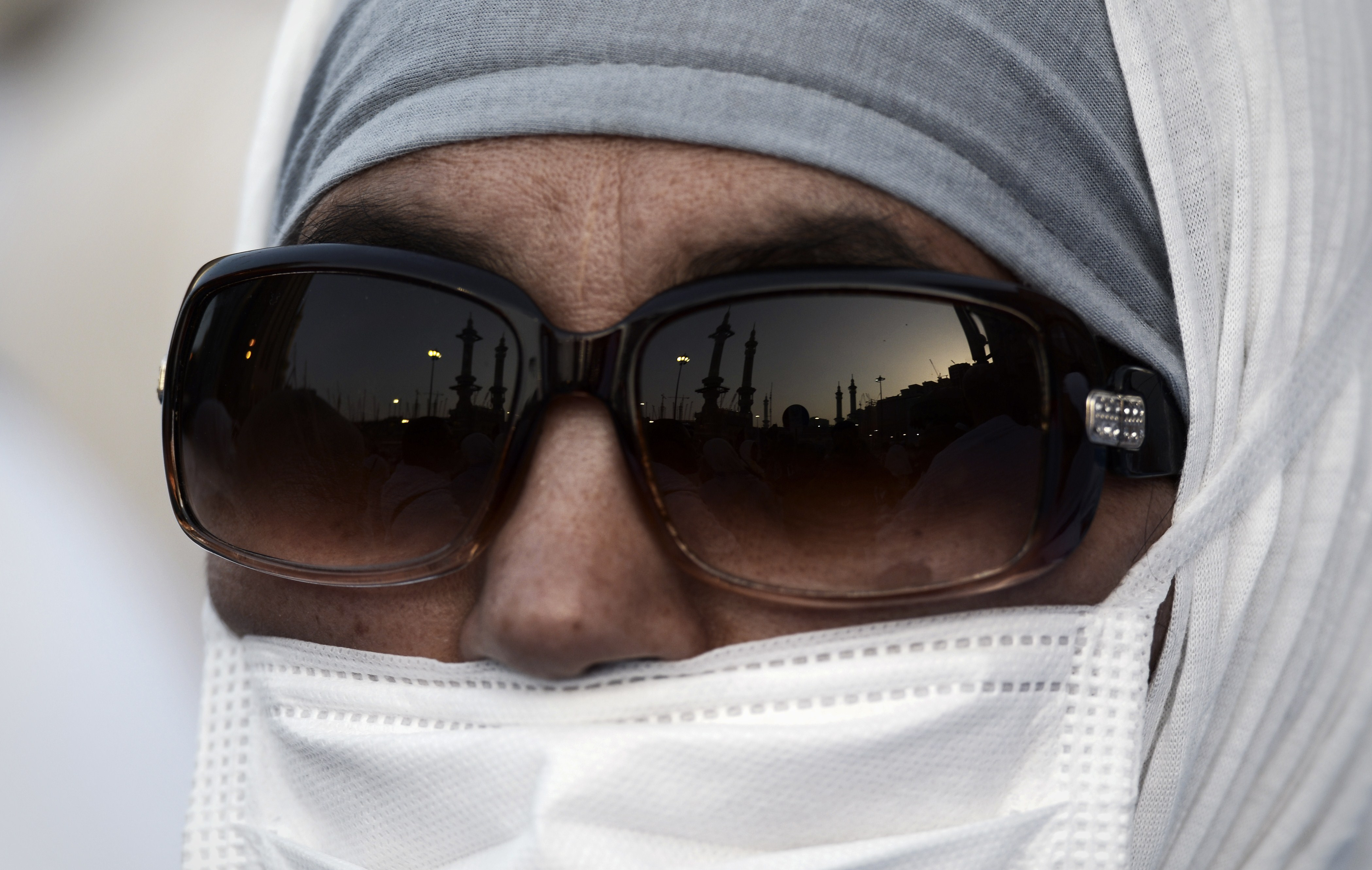 A Muslim pilgrim wearing a mask arrives for a prayer at Mecca's Grand Mosque, on September 29, 2014.