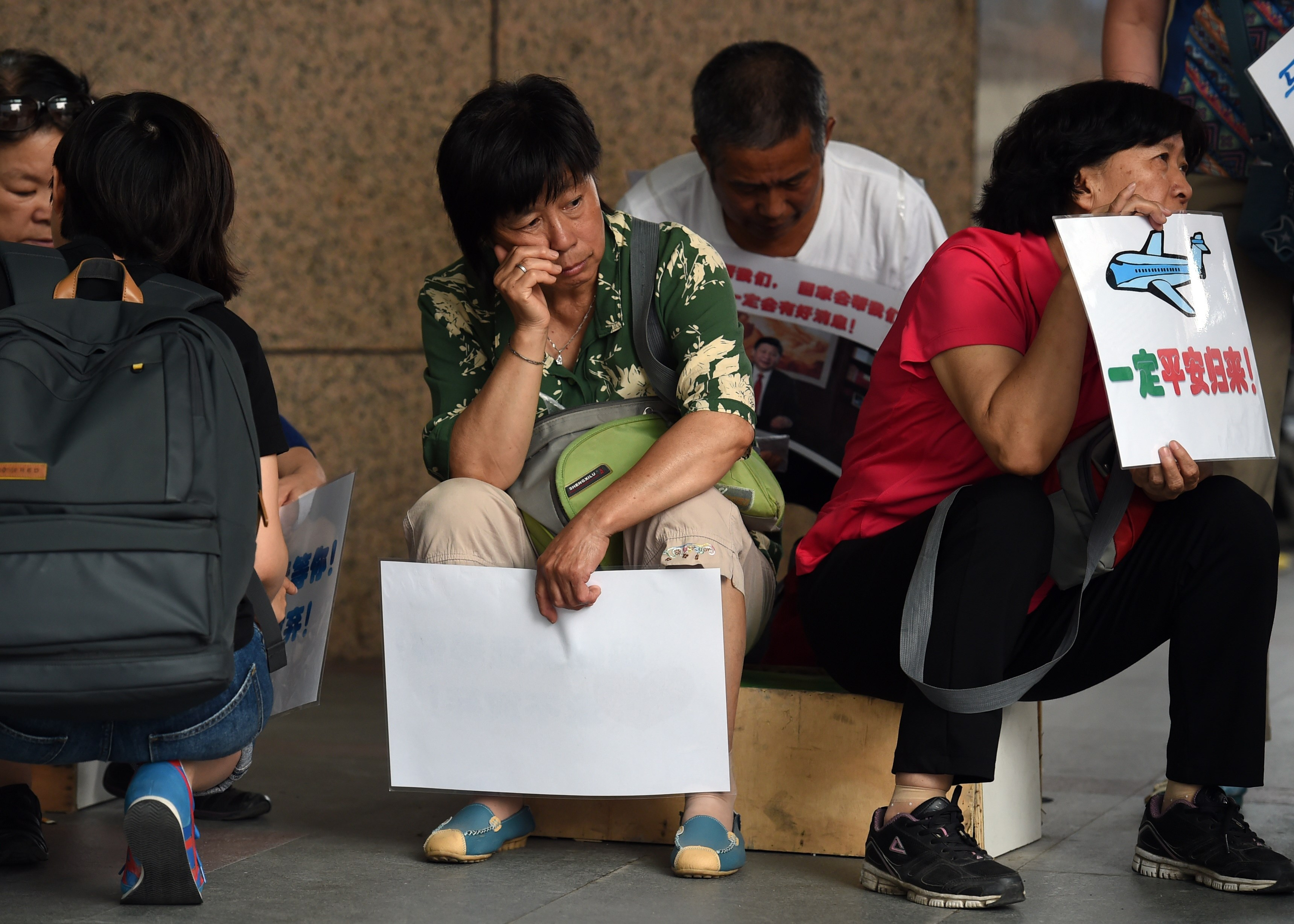 Relatives of passengers on missing Malaysia Airlines MH370 wait outside the Malaysia Airlines office in Beijing on August 6, 2015.  Debris found on a remote island a week ago is from flight MH370, Malaysia's prime minister said, confirming that the plane which mysteriously disappeared 17 months ago met a tragic end in the Indian Ocean.    AFP PHOTO / GREG BAKER        (Photo credit should read GREG BAKER/AFP/Getty Images)