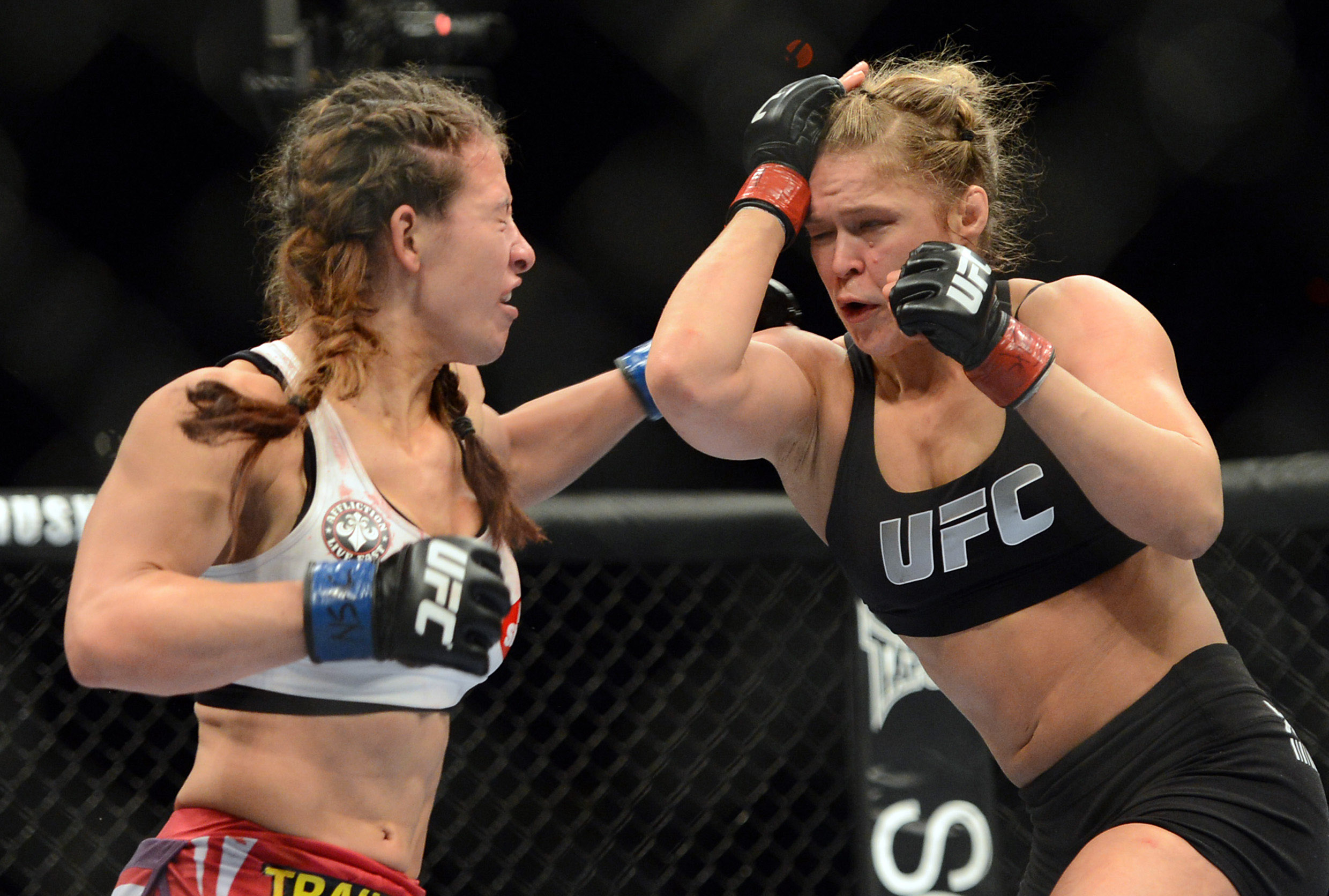 Ronda Rousey (red gloves) and Miesha Tate (blue gloves) fight during the UFC women's bantamweight championship bout at the MGM Grand Garden Arena in Las Vegas on Dec. 28, 2013.