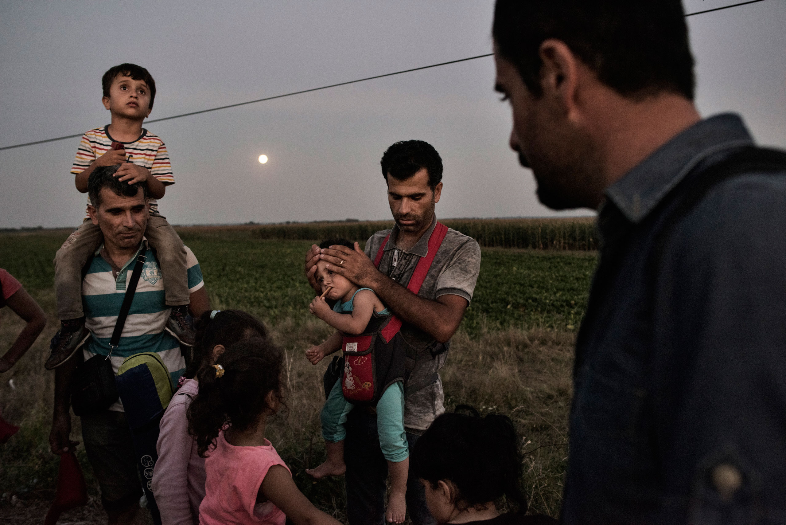 A Syrian family prepares to turn themselves into a Hungarian detention facility for migrants arriving in the European Union in Roszke, Hungary on Aug. 29, 2015.