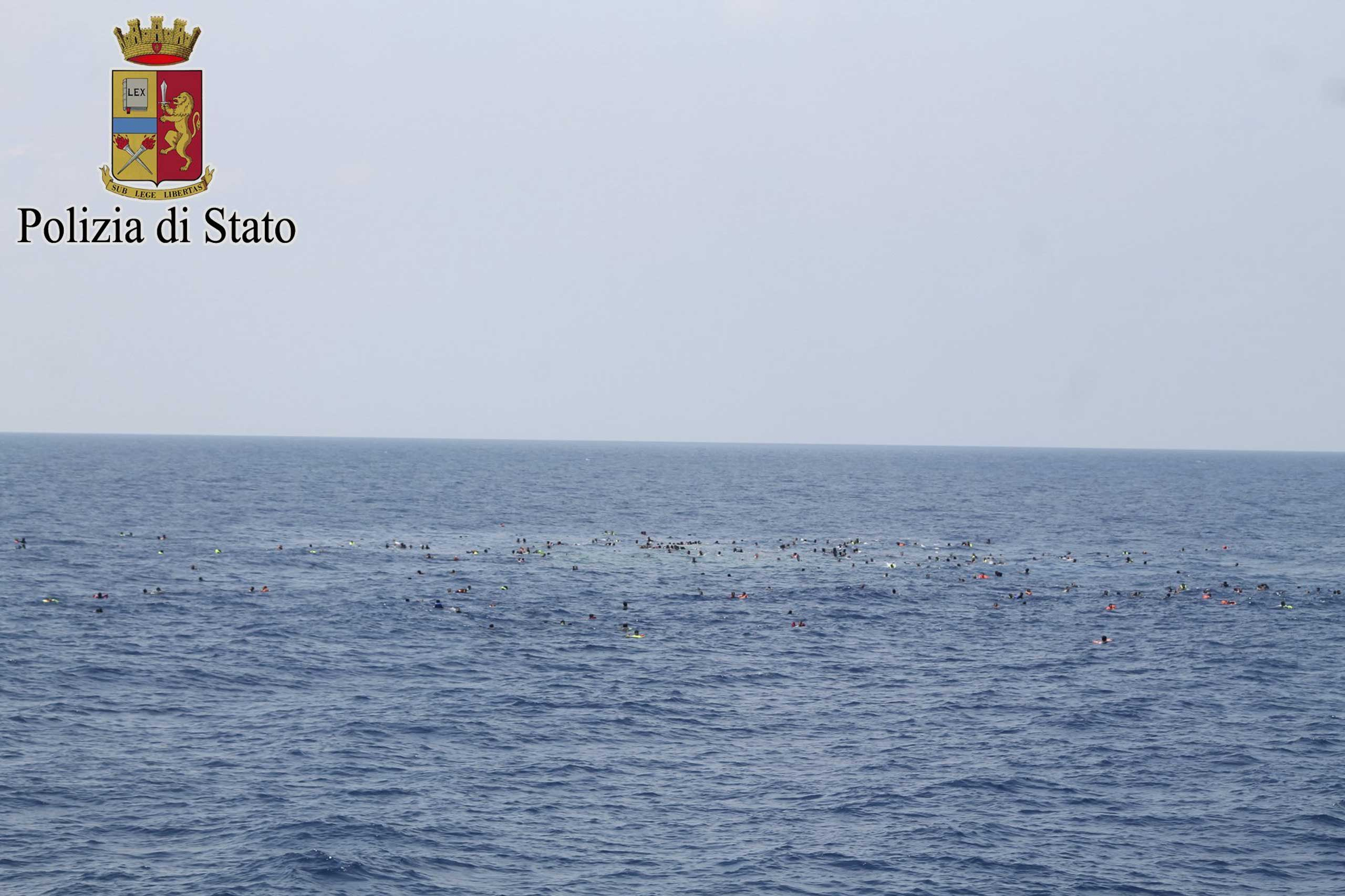 Surviving migrants are seen swimming in the area where their wooden boat capsized and sank off the coast of Libya on Aug. 5, 2015.