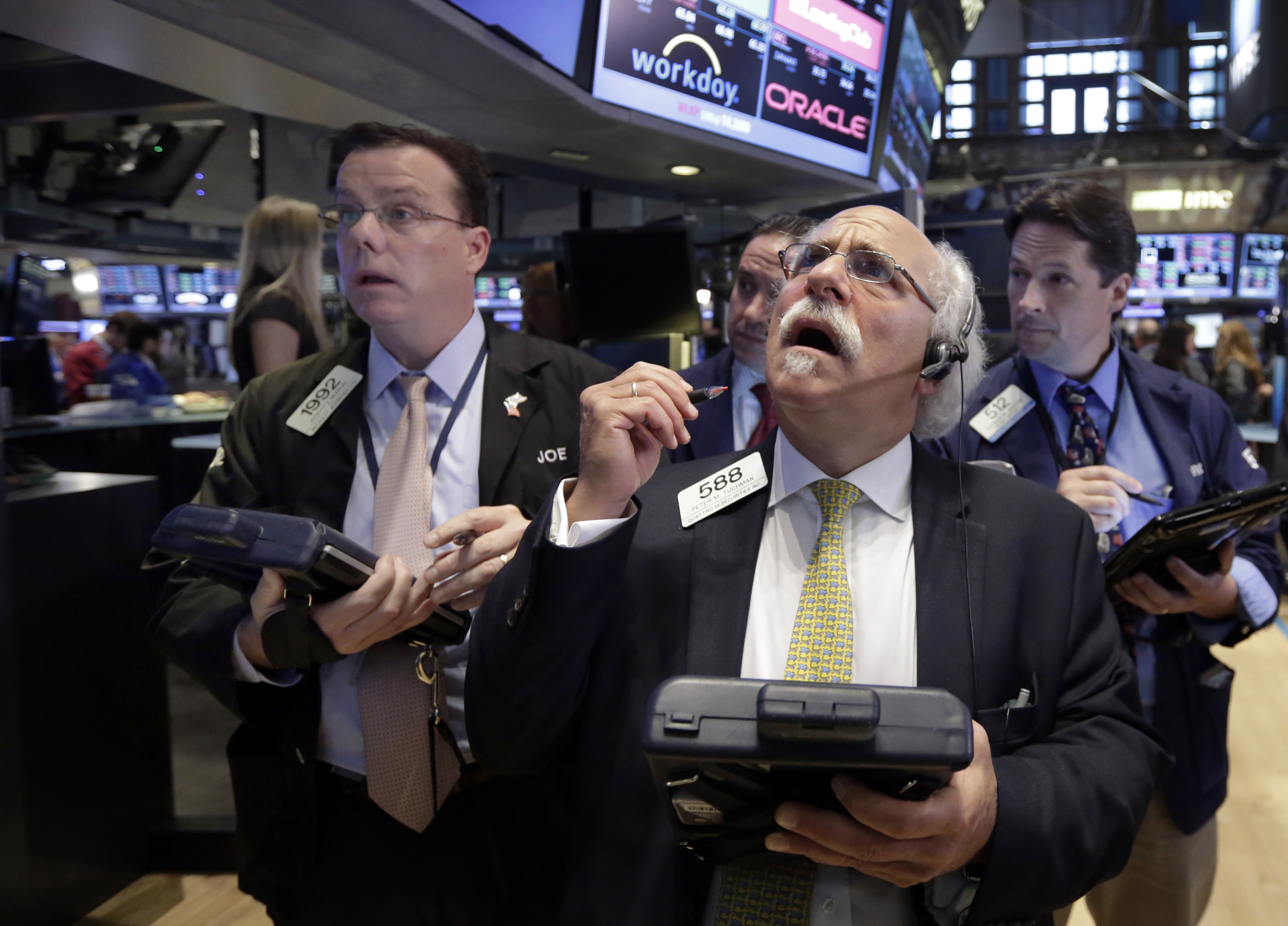 Peter Tuchman, foreground right, works with fellow traders on the floor of the New York Stock Exchange on Aug. 24, 2015.