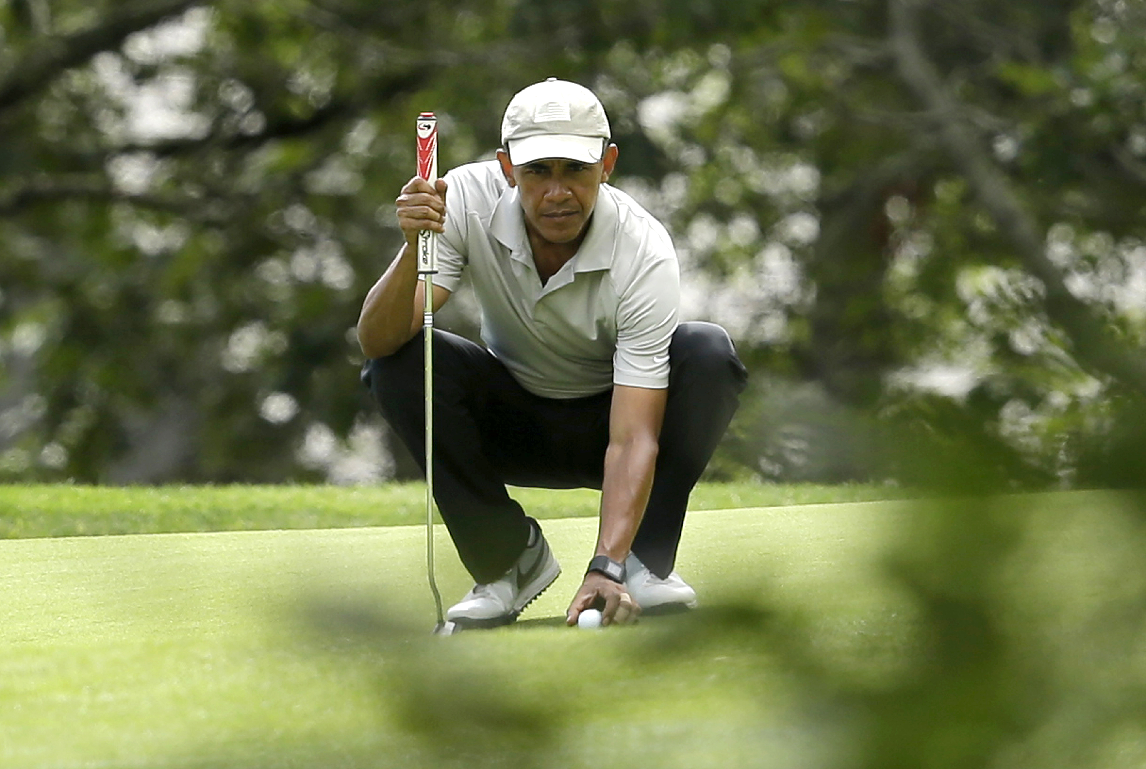 President Barack Obama places his ball on the green before putting while golfing on Aug. 23, 2015, at Farm Neck Golf Club, in Oak Bluffs, Mass., on the island of Martha's Vineyard.