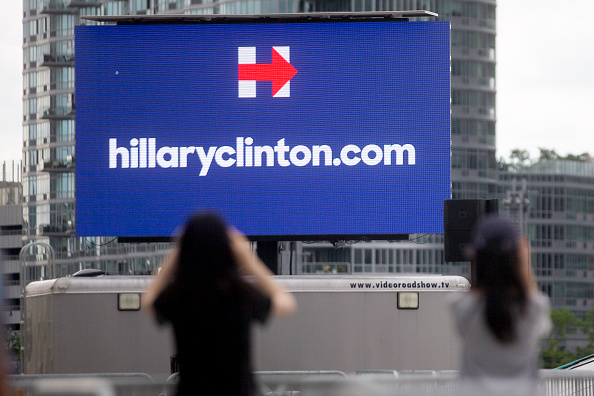 Visitors take a photograph of a Hillaryclinton.com billboard before the first 2016 Democratic candidate Hillary Clinton campaign rally at Four Freedoms Park on Roosevelt Island in New York, U.S., on Saturday, June 13, 2015.