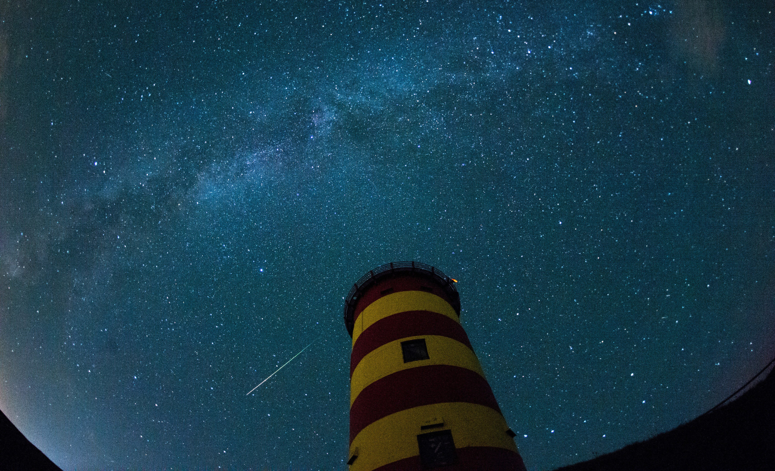 13 Aug 2015, Germany --- A shooting star lights up the night sky above the Pilsum lighthouse in Pilsum, Germany, 12 August 2015. Additionally towards the top of the image the Milky Way can be seen. On the nights of the 12 and 13 August 2015 the shooting stars of the Perseid stream are to unfold at maximum splendor. Photo: Matthias Balk/dpa --- Image by © Matthias Balk/dpa/Corbis