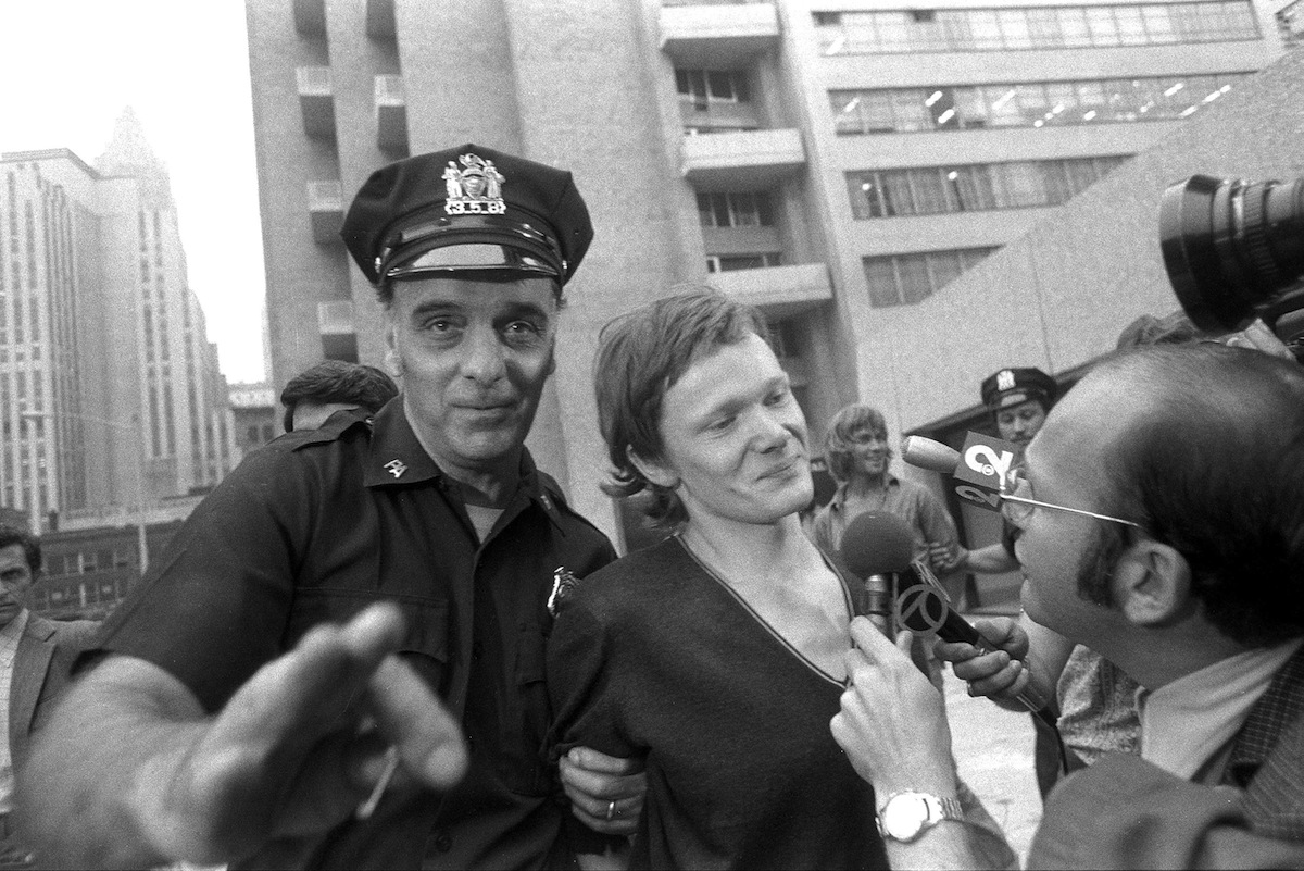Philippe Petit (center) answers reporter's questions on Aug. 7, 1974, as he is escorted from Beekman Hospital by Port Authority police officer in New York City. Petit was arrested after he walked a tightrope between the two towers of the World Trade Center.