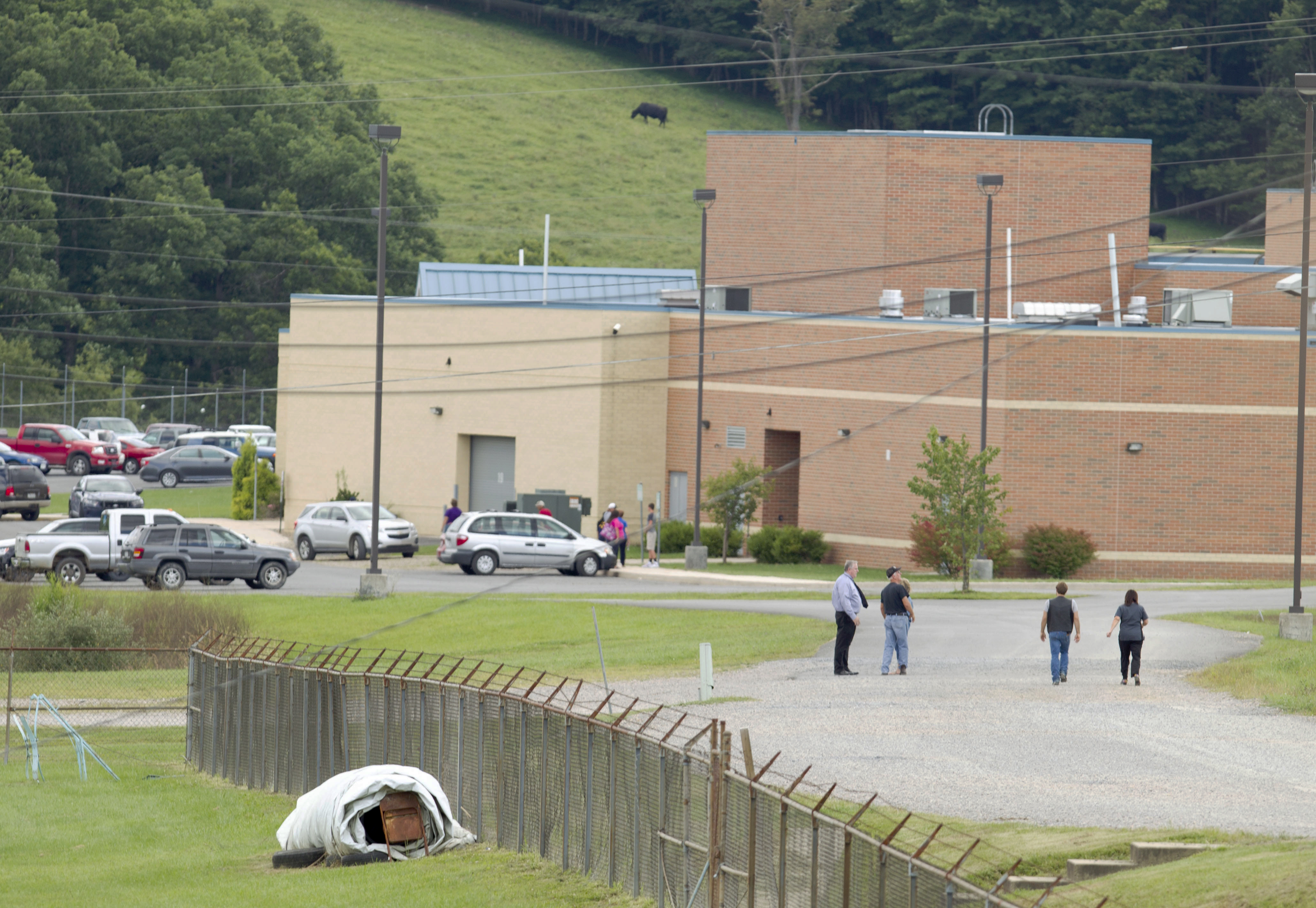Parents of children from Philip Barbour High School in Philippi, W.Va., walk to the school to meet up with their children that were evacuated after a  hostage-like  situation occurred in the school on Aug. 25, 2015.