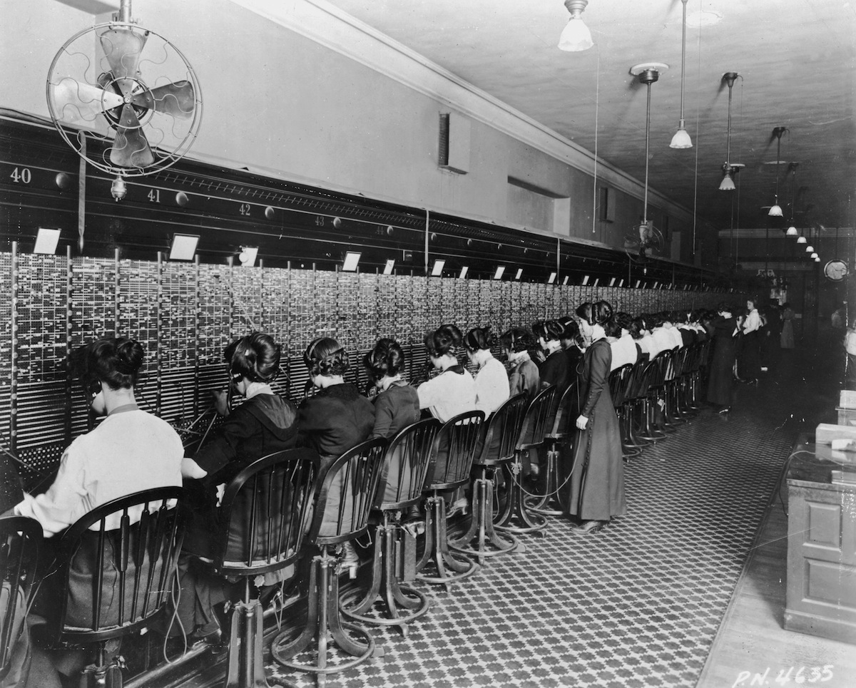 Telephone operators sitting in front of a long switchboard at the Cortlandt Exchange in New York City around the turn of the century