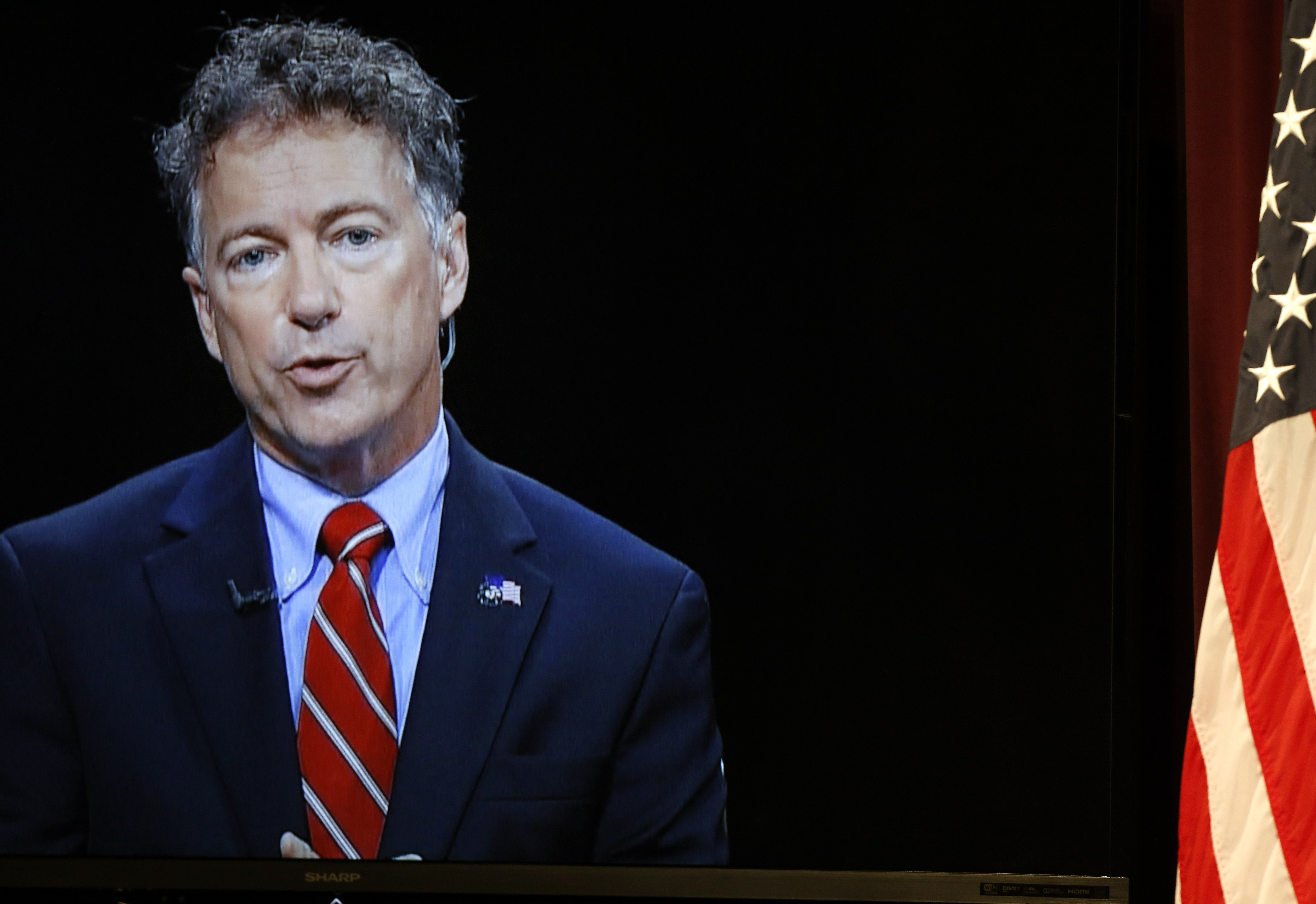 Republican presidential candidate, Sen. Rand Paul, R-Ky., shown on a video screen from C-SPAN's Washington studio, speaks during a forum on Aug. 3, 2015, in Manchester.