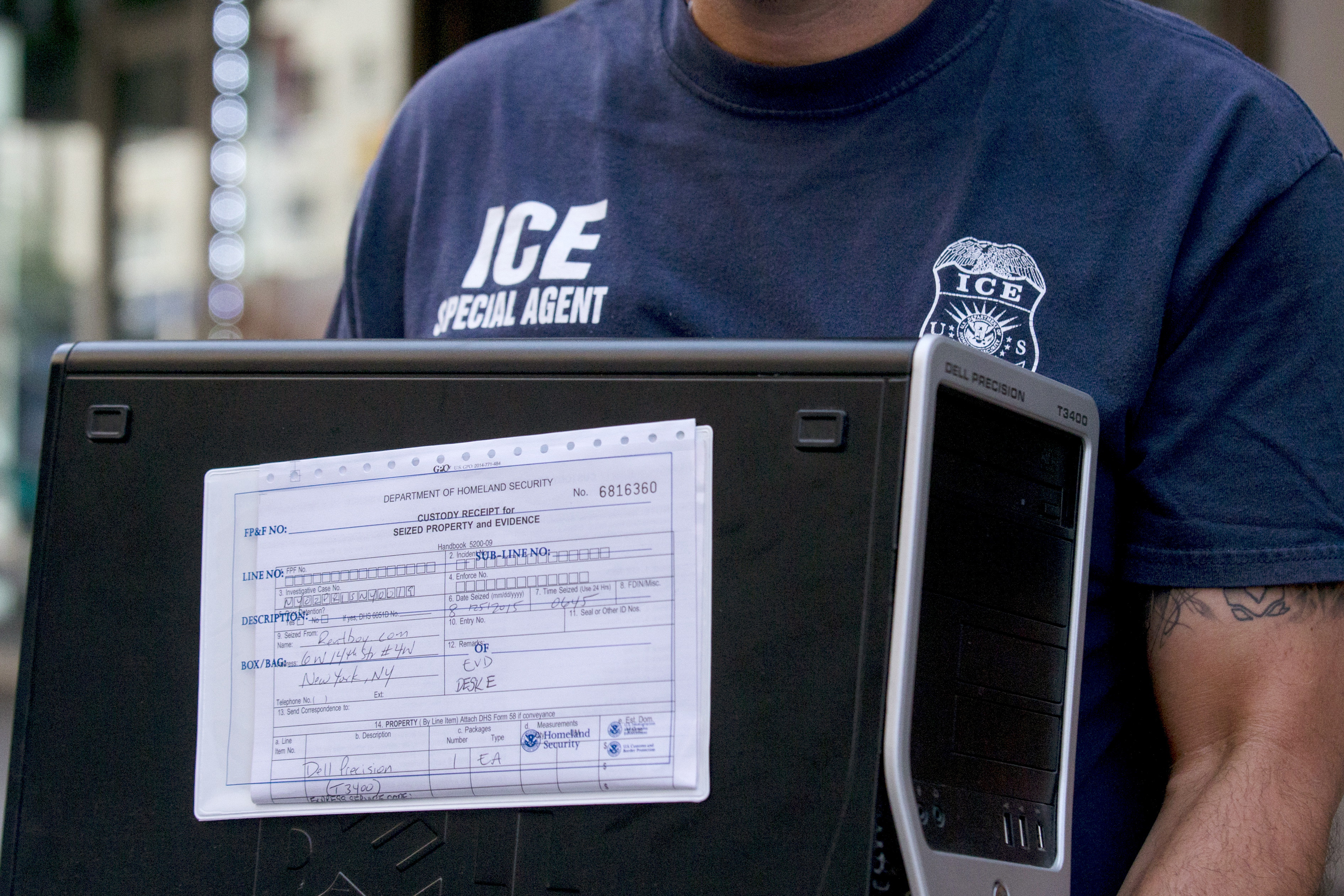 A federal law enforcement officer carries a computer labeled as evidence from the Manhattan offices of Rentboy.com in New York City on Aug. 25, 2015.