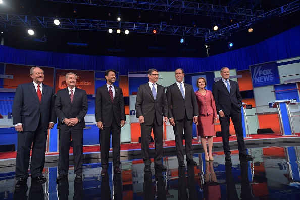 Republican presidential hopefuls (L-R) Jim Gilmore, Lindsey Graham, Bobby Jindal, Rick Perry, Rick Santorum, Carly Fiorina and George Pataki arrive on stage for the start of the Republican presidential primary debate on August 6, 2015 at the Quicken Loans Arena in Cleveland, Ohio.