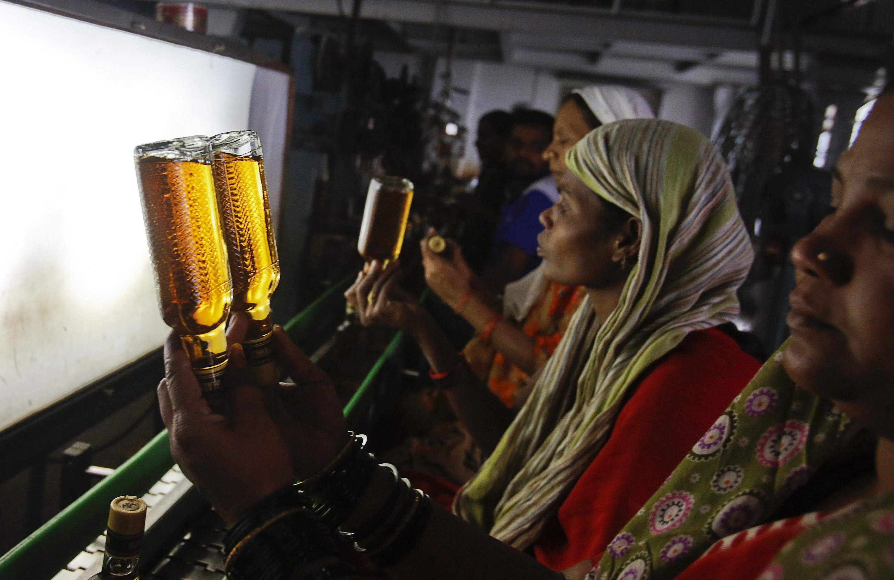 A bottling plant worker checks bottles of Black Power whisky for impurities at a Tilaknagar Industries distillery and bottling unit in Srirampur, about 186 miles northwest of Mumbai, January 28, 2013