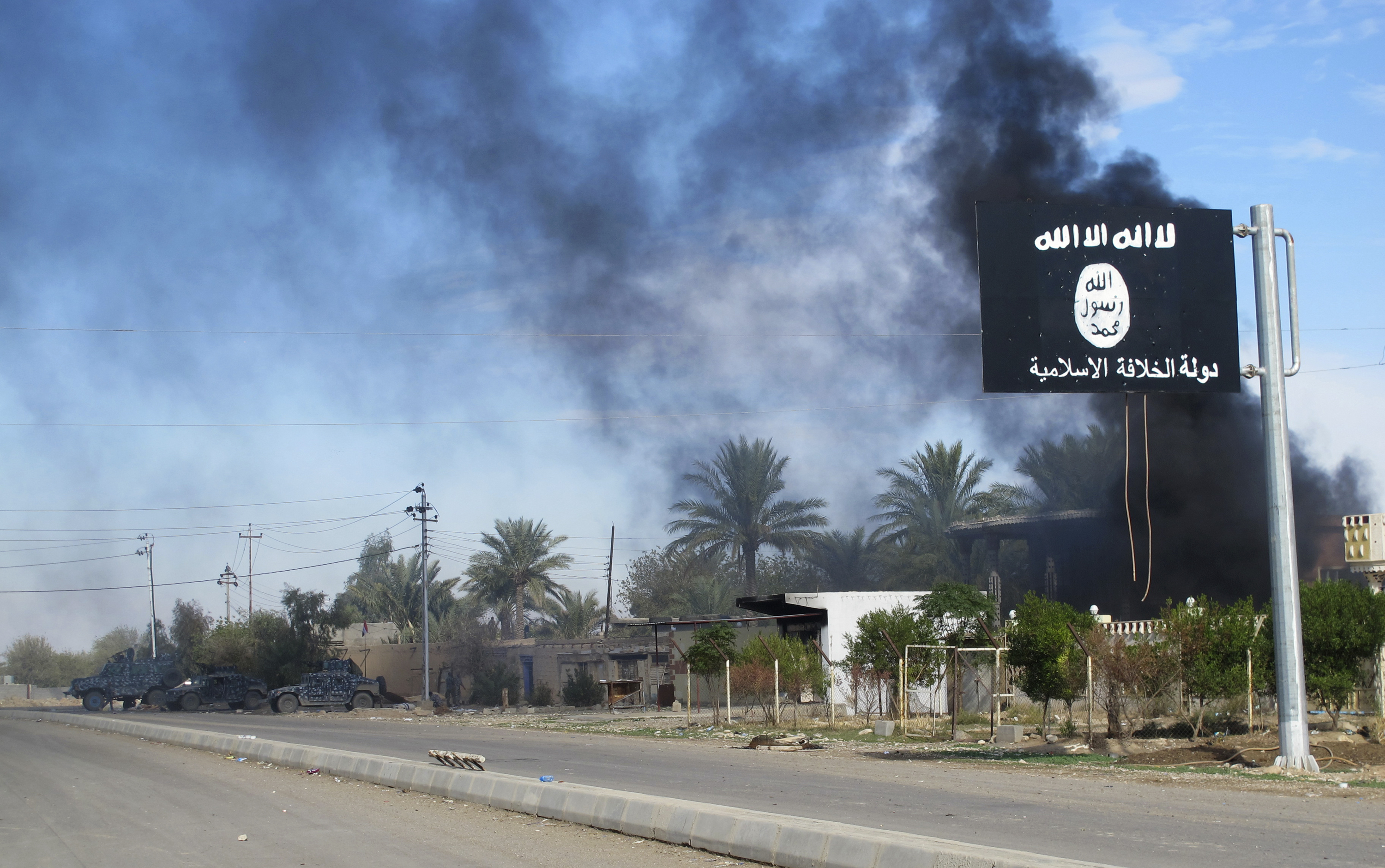 Smoke raises behind an Islamic State of Iraq and Greater Syria flag after Iraqi security forces and Shi'ite fighters took control of Saadiya in Diyala province from ISIS militants on Nov. 24, 2014