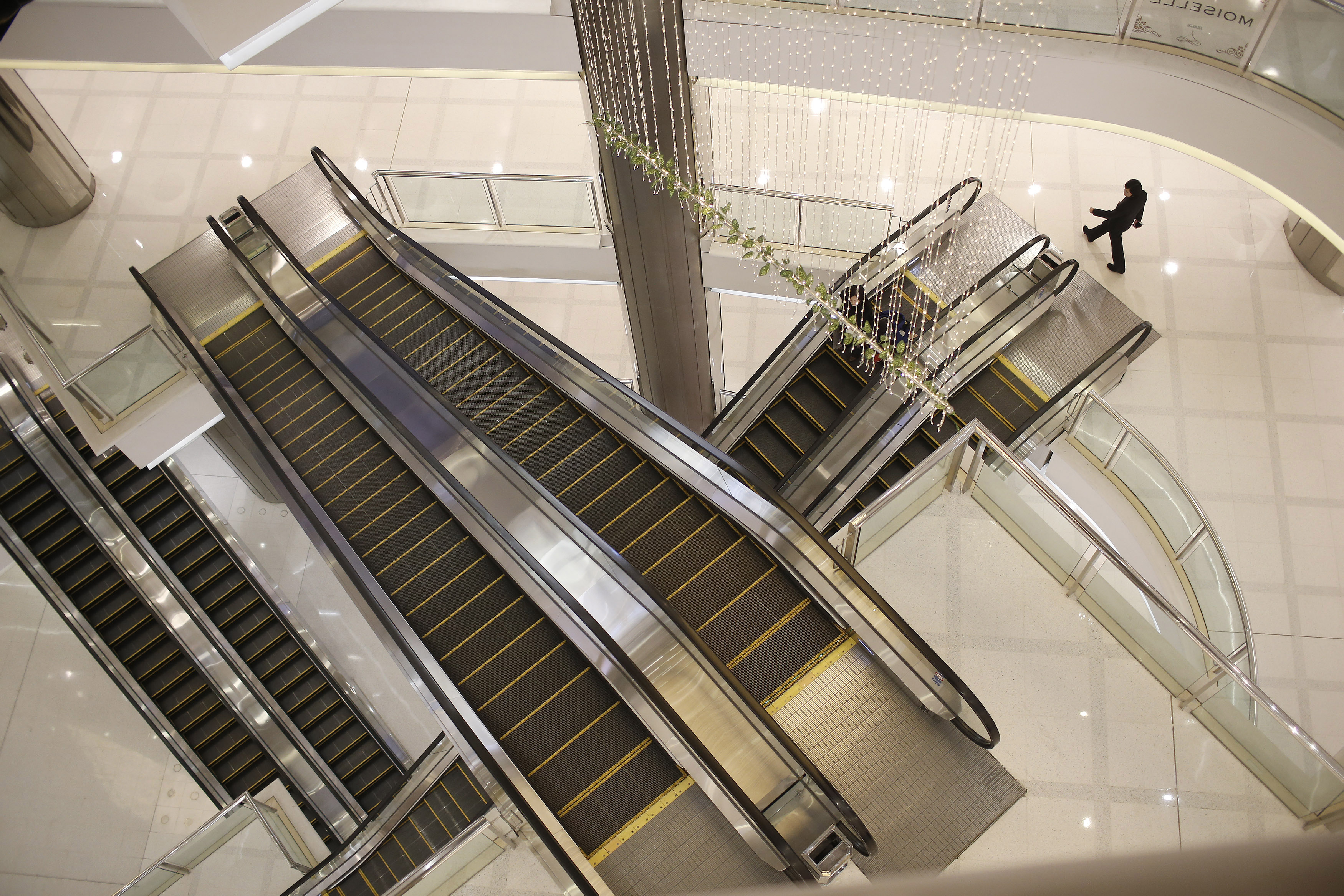 A woman walks next to escalators at a department store in Shanghai, March 8, 2015.