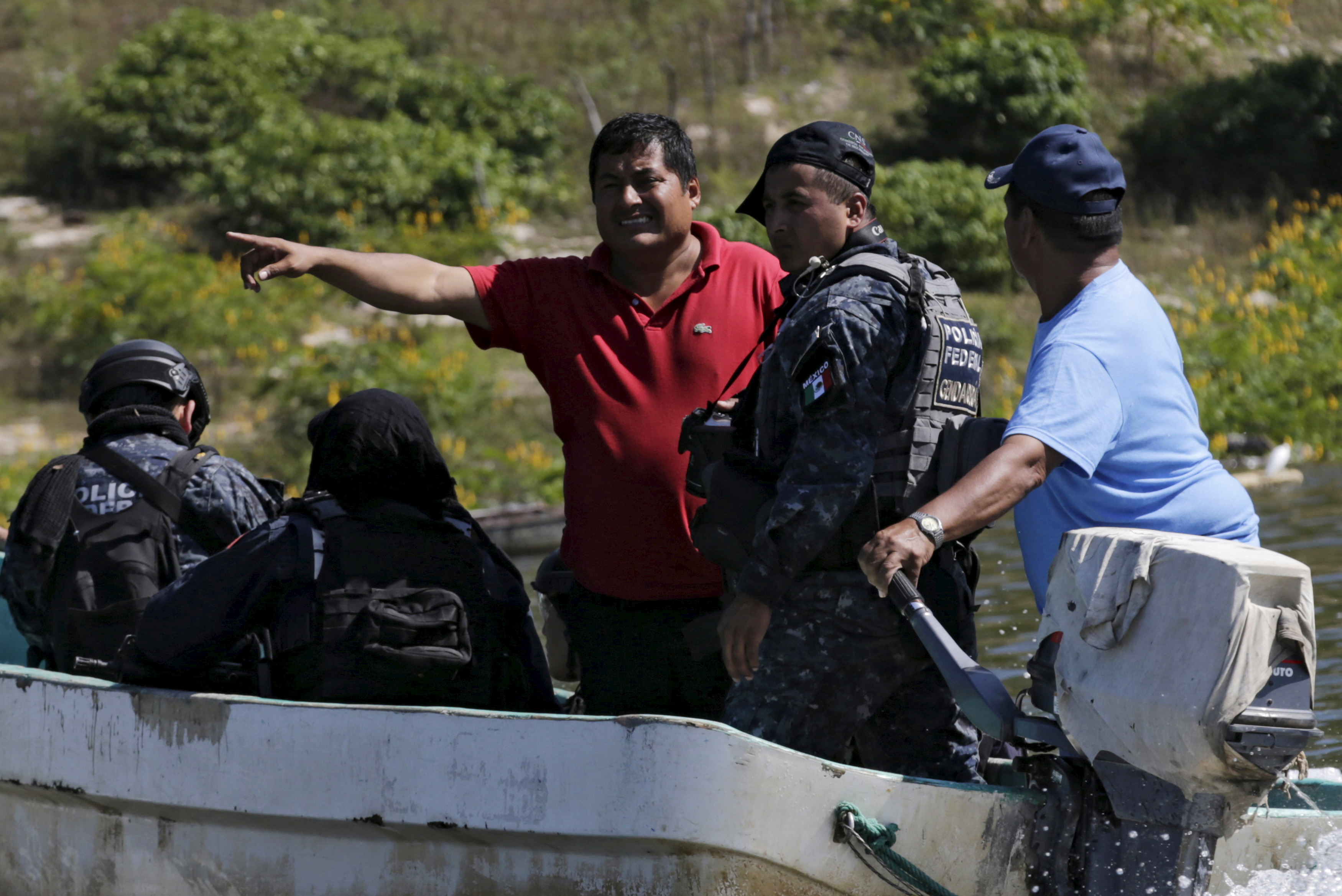 Miguel Angel Jimenez (in red), leader of the community police of Guerrero State (UPOEG), speaks with a federal police on a boat as they seek for the 43 Ayotzinapa students' missing, in Acatlan,  Guerrero, on October 30, 2014.