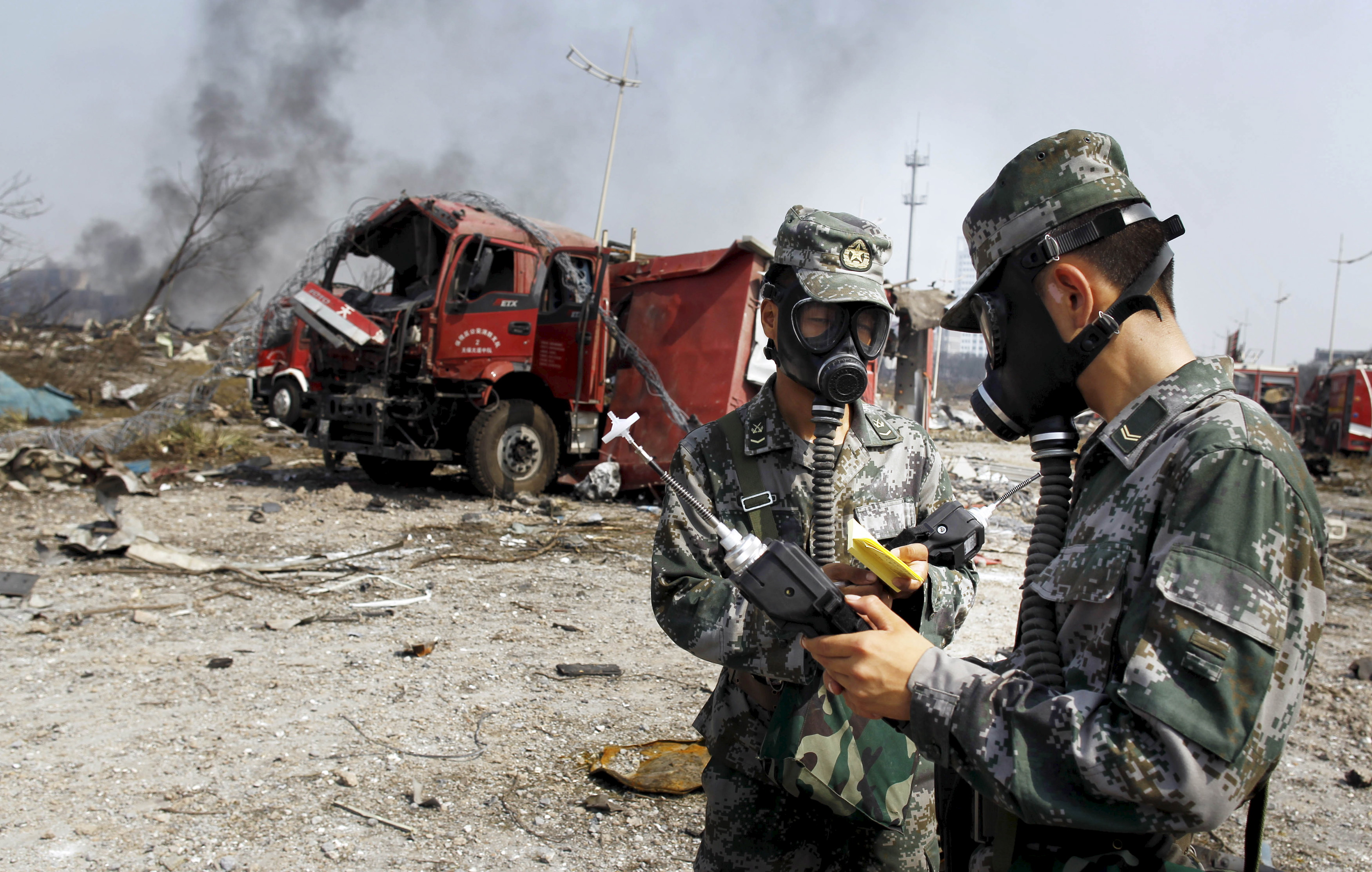 Soldiers of the People's Liberation Army antichemical-warfare corps work next to a damaged firefighting vehicle at the site of the Aug. 12 explosions at Binhai new district in Tianjin, China, on Aug. 16, 2015.