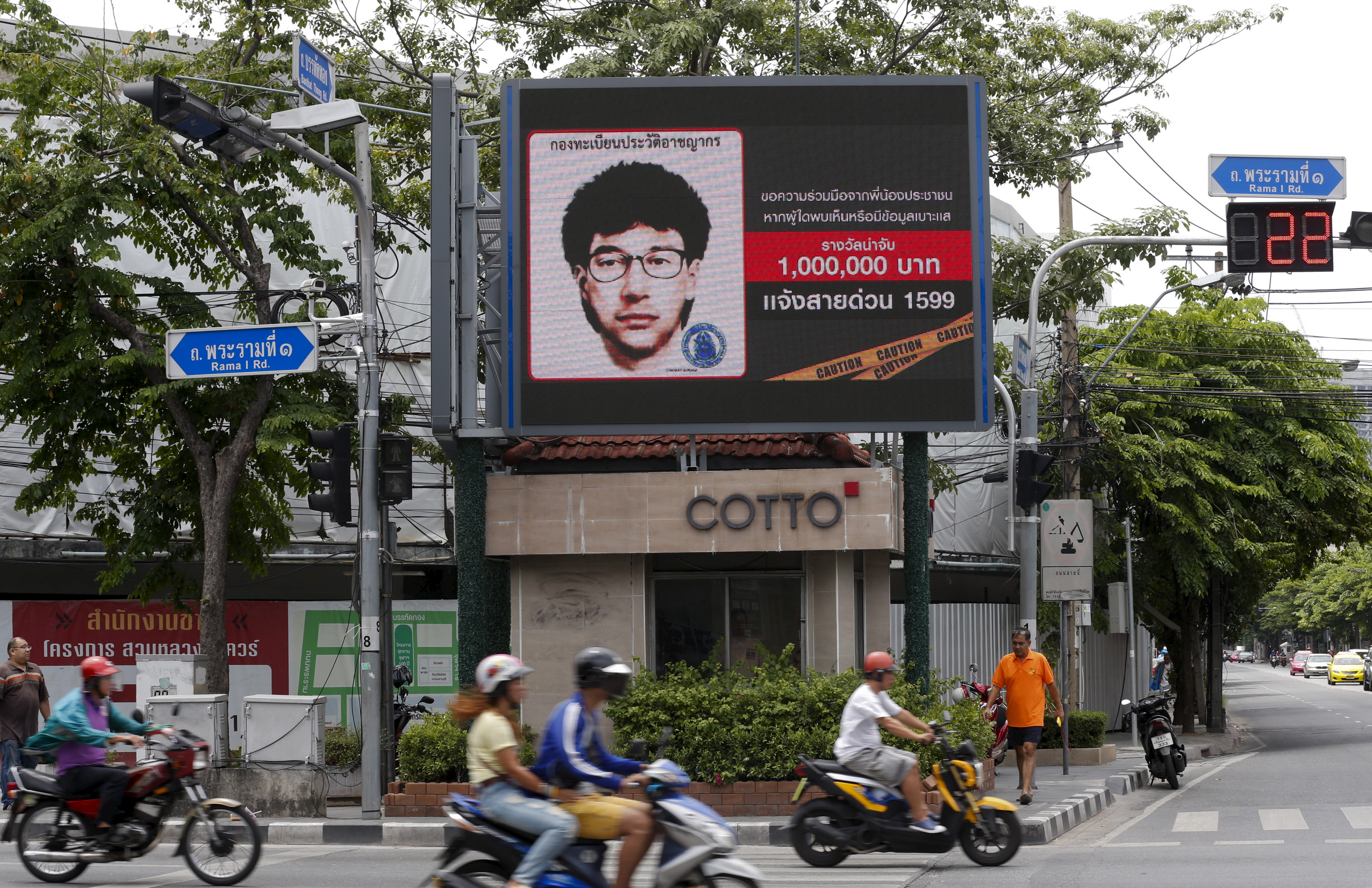 People ride their motorcycles past a digital billboard showing a sketch of the main suspect in the Aug. 17 attack on Erawan shrine in Bangkok on Aug. 23, 2015