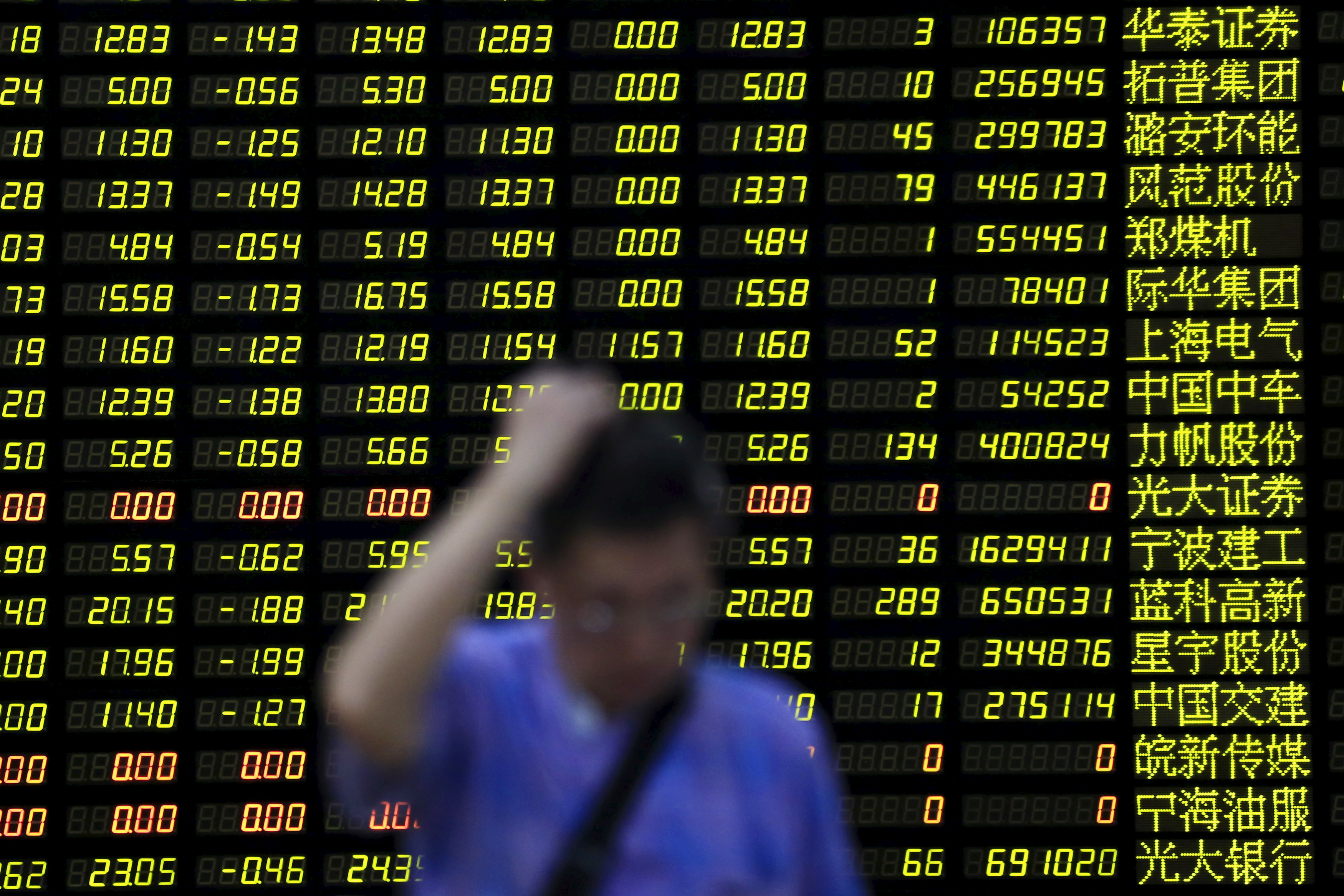 An investor stands in front of an electronic board showing stock information at a brokerage house in Shanghai on Aug. 24, 2015